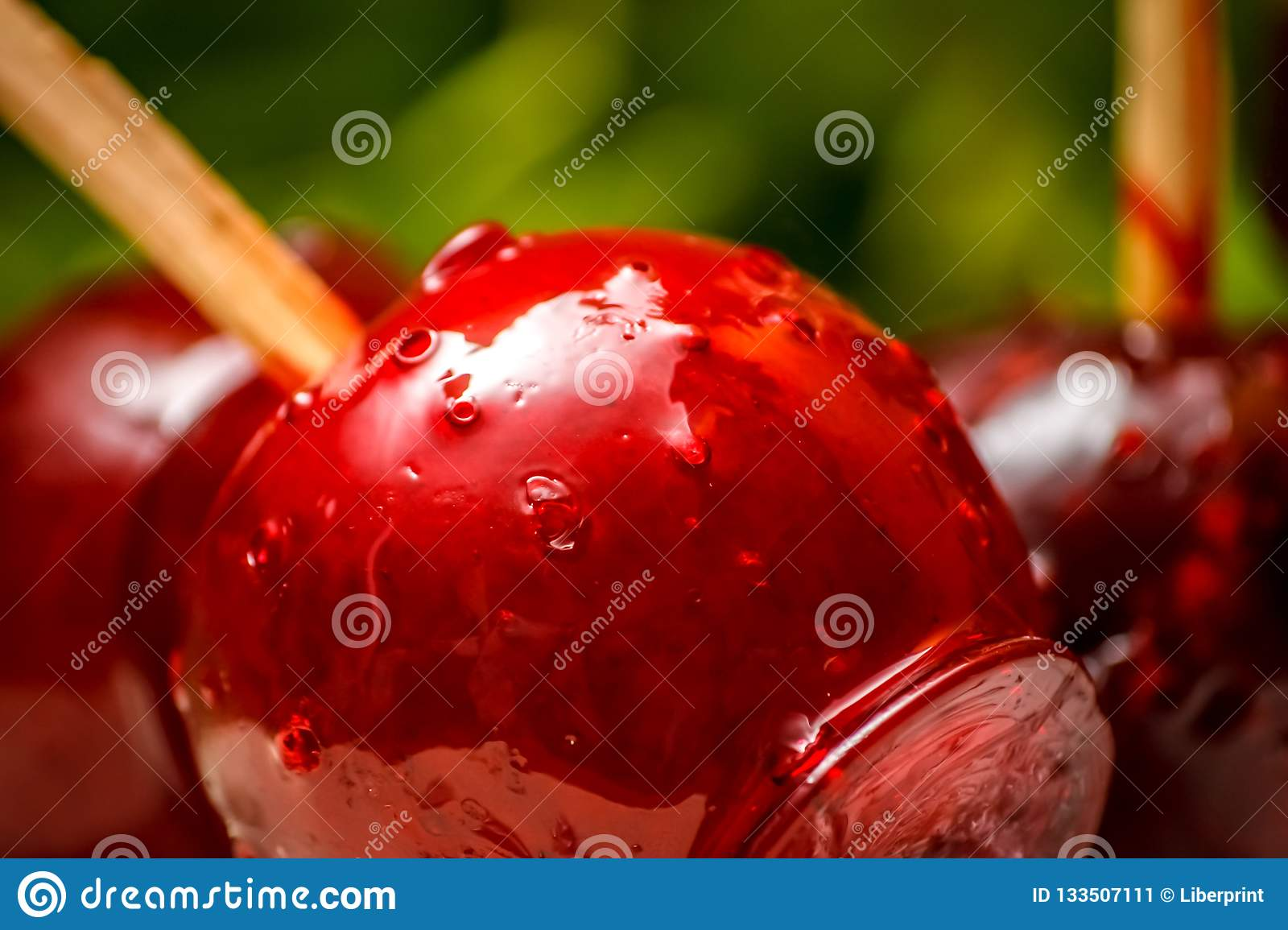 Red candy or toffee apple with green liana vine in the background.