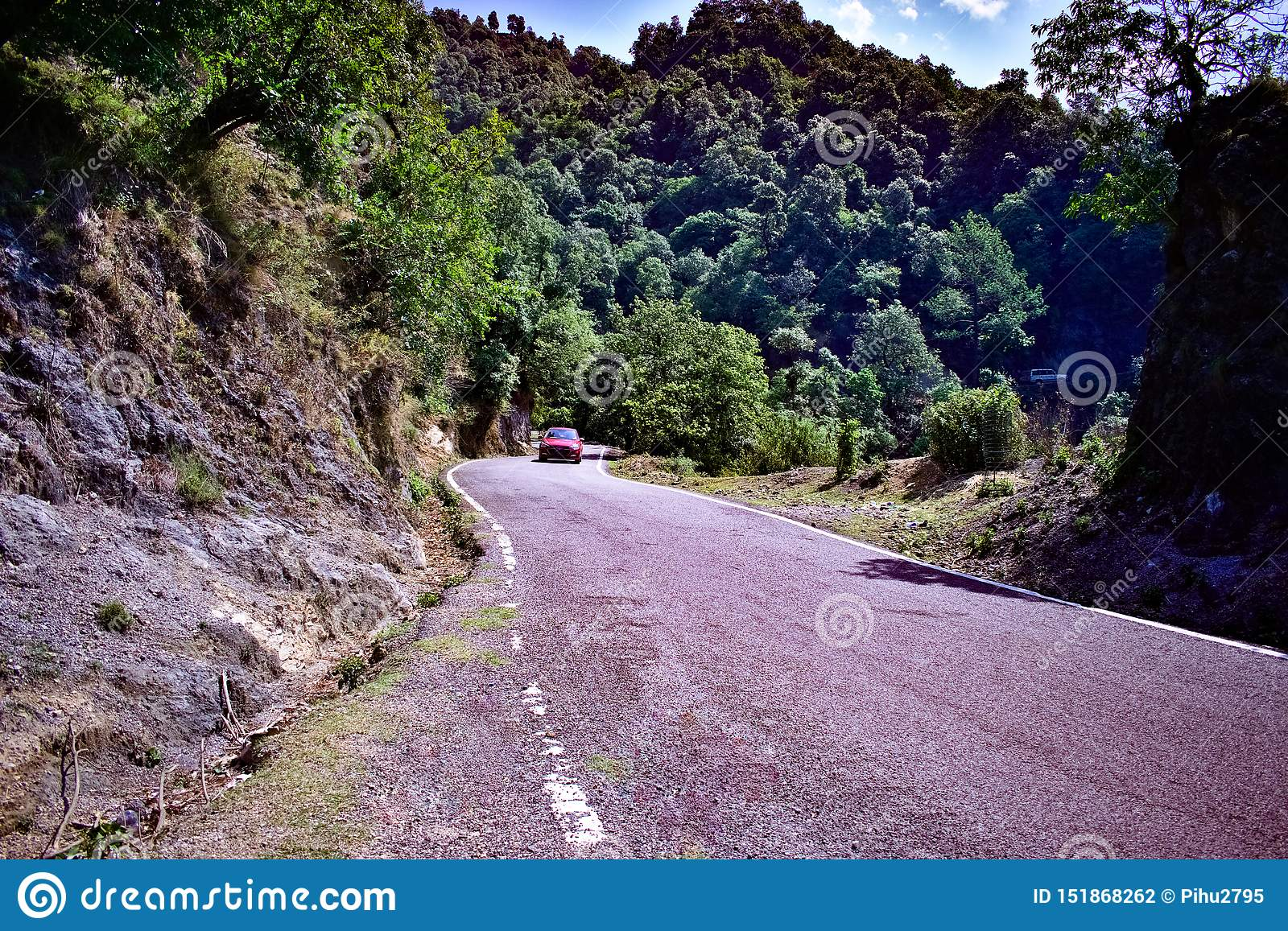 Red car speeding through a road in the mountains driving red car through the hills on vacation travelling in the himalayan mountai
