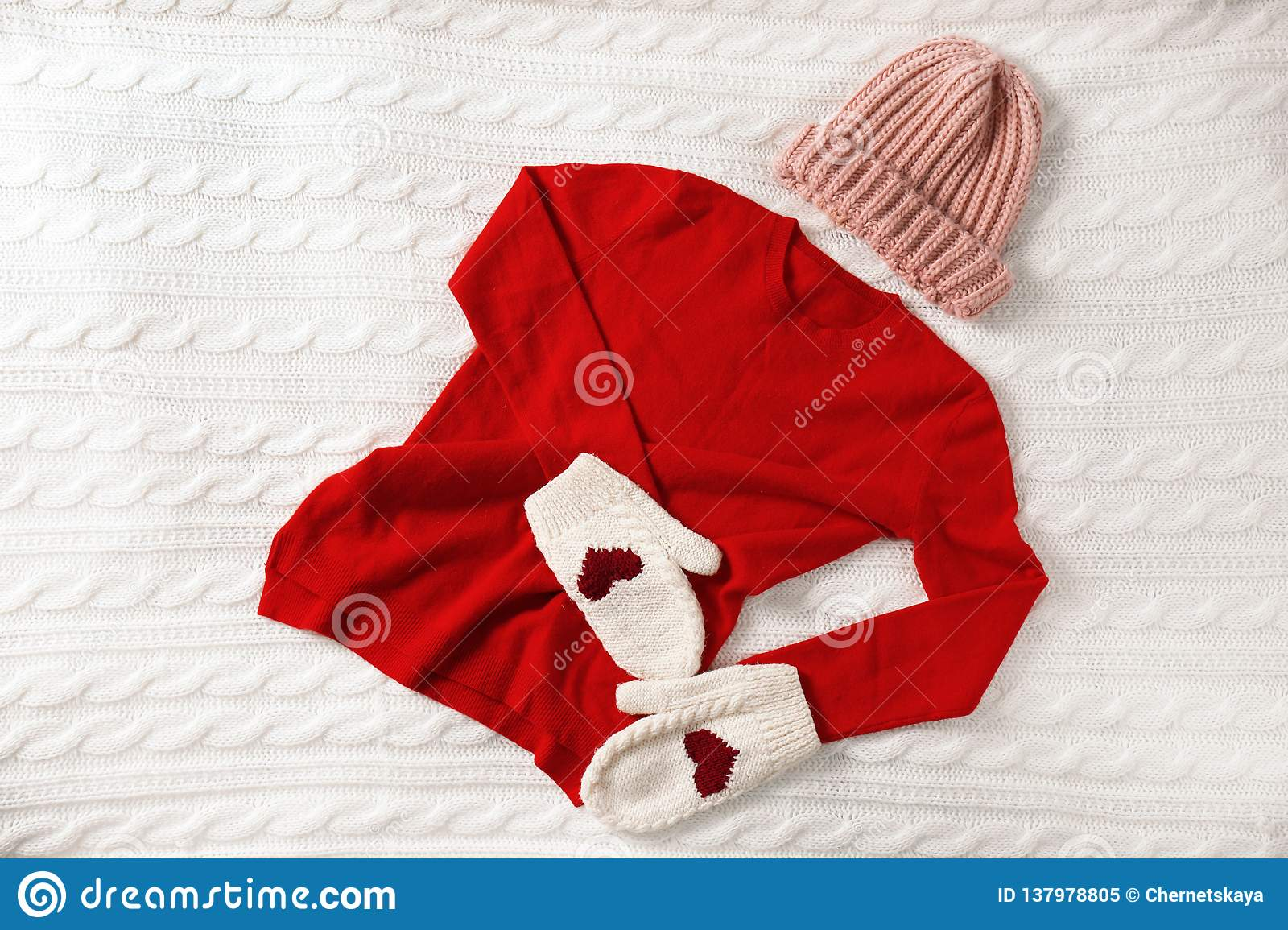 Red cashmere sweater, hat and mittens on knitted plaid