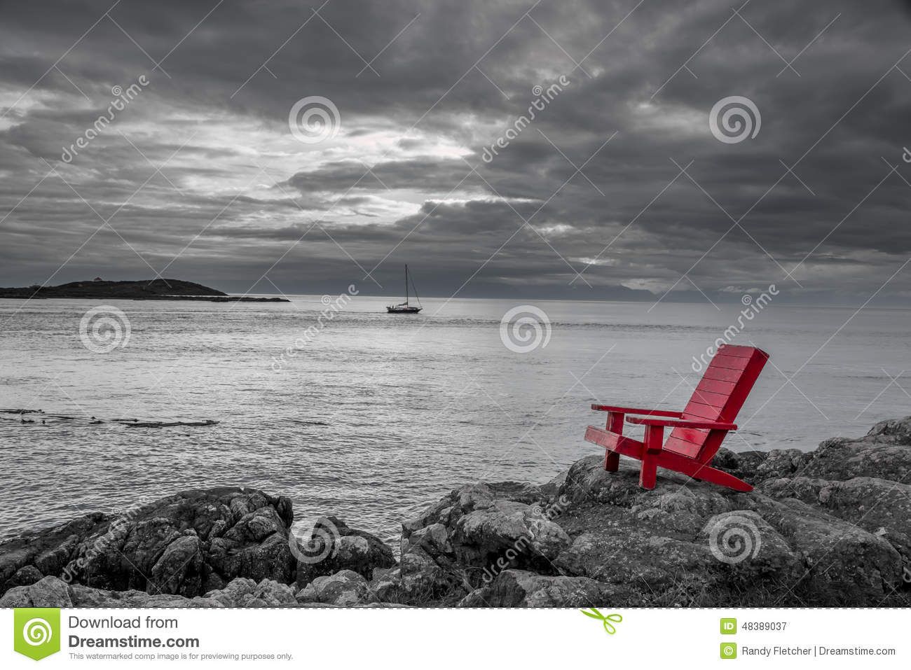 Red adirondack chair contrasts with a stormy black and white ocean