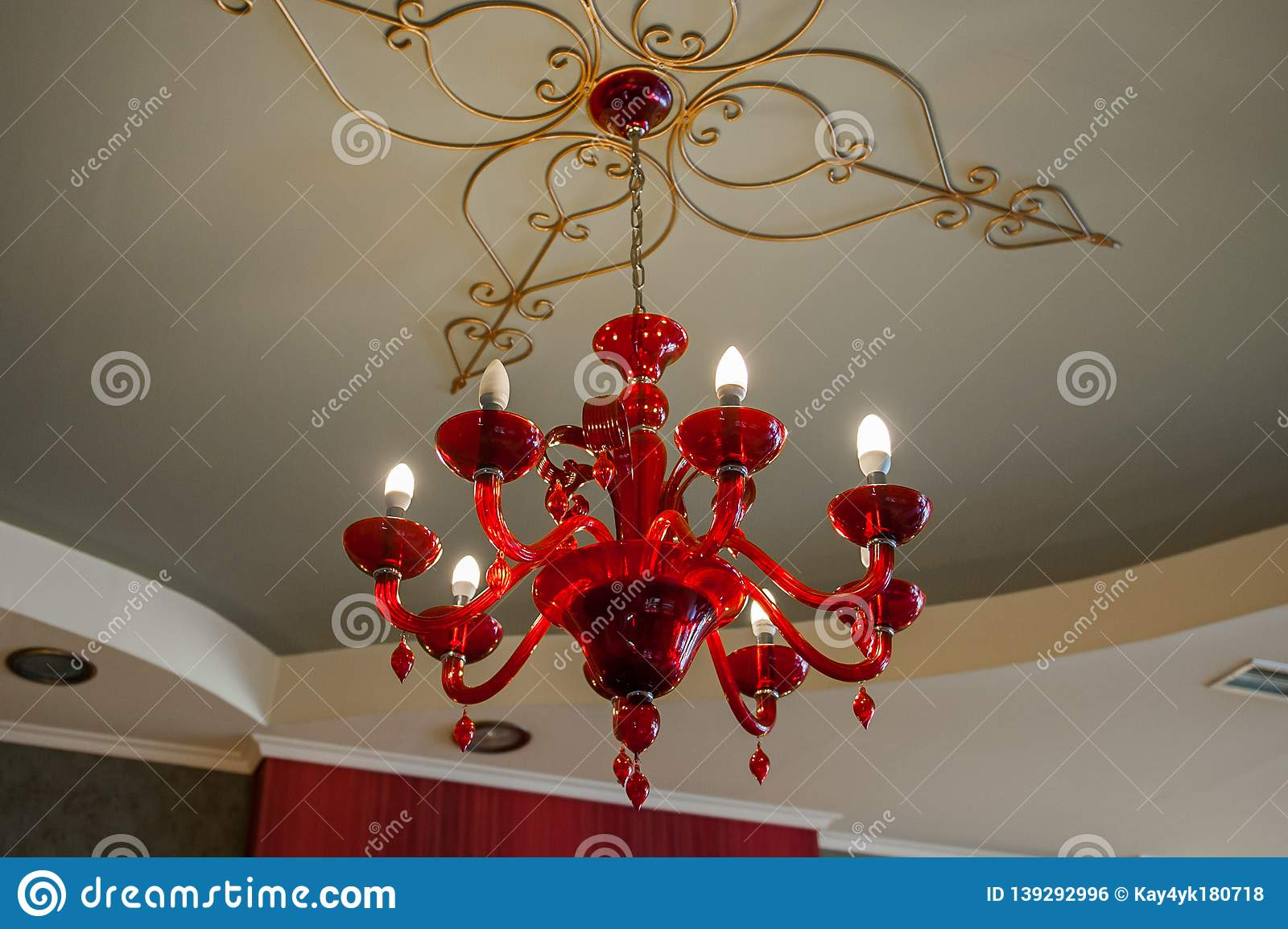 Red chandelier on a patterned ceiling in a dark room, glowing bulbs on it