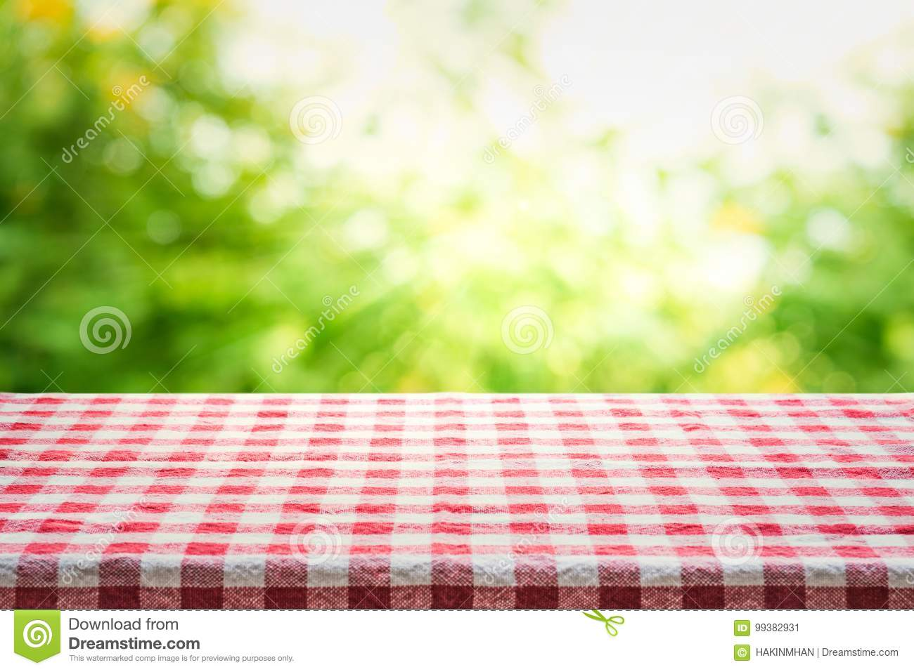 Red checkered tablecloth texture top view with abstract green bokeh