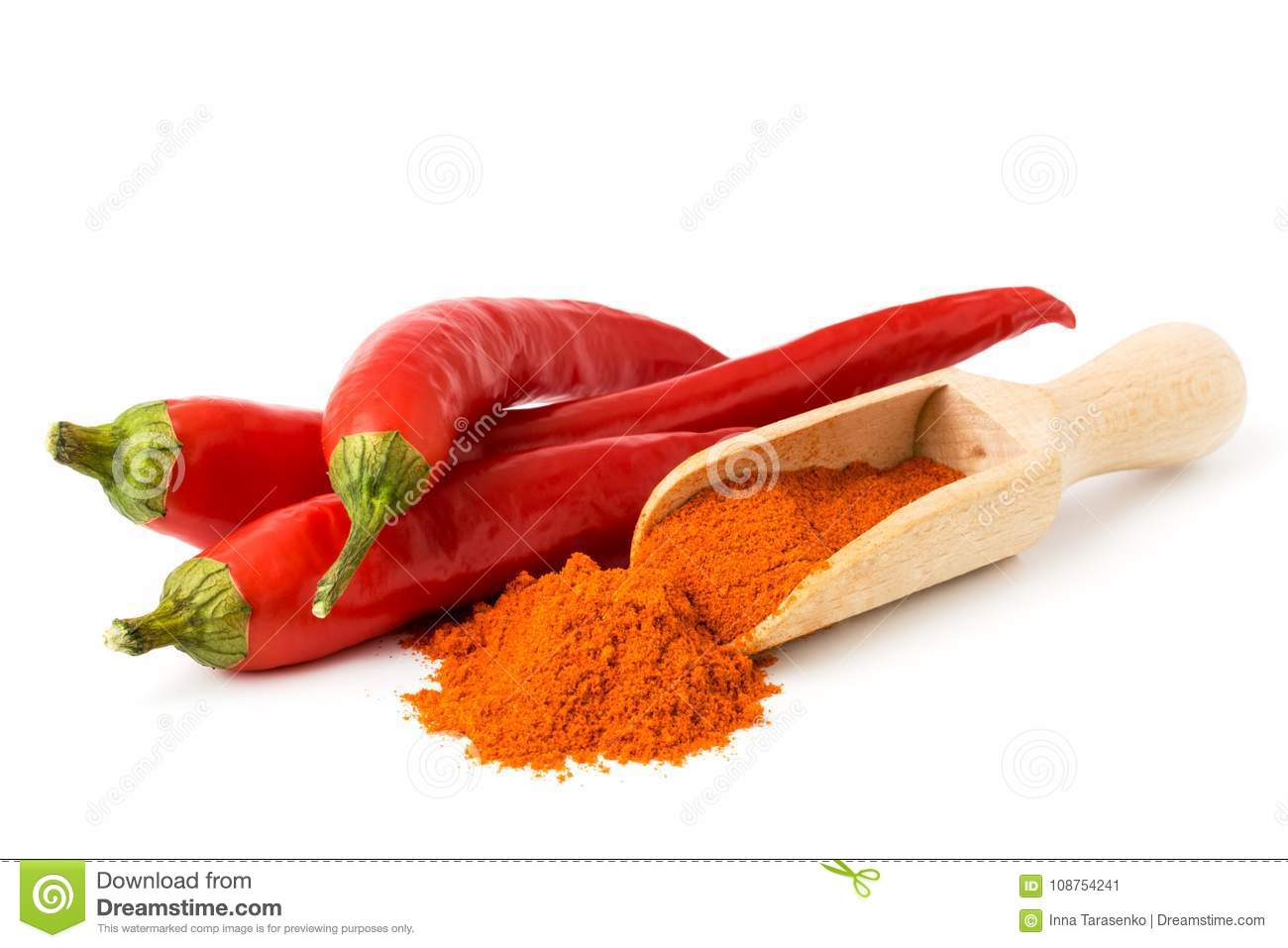 Red chili pepper and ground pepper in a wooden spoon, on white background.