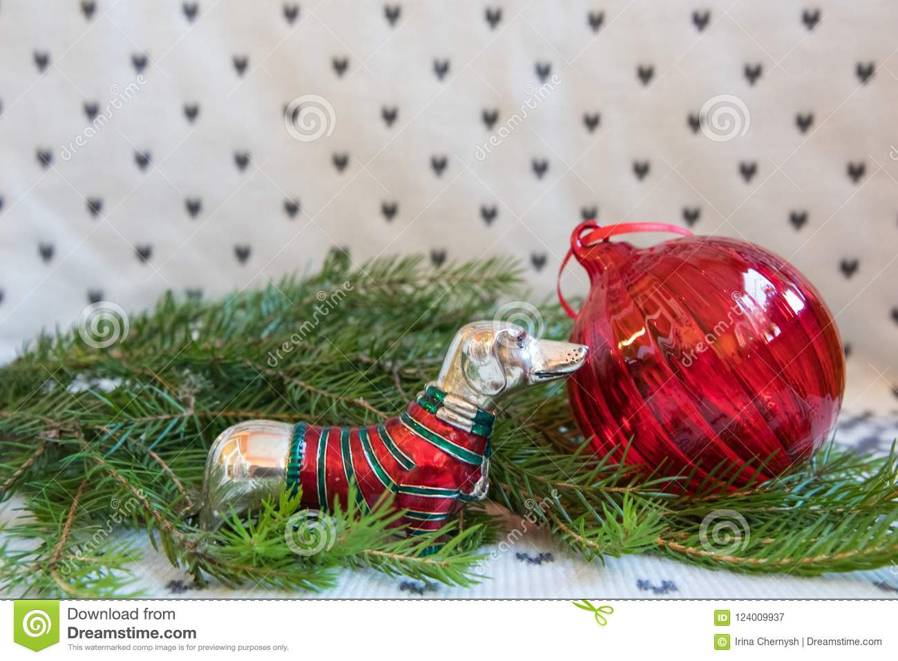 Red Christmas ball and dachshund in red-green sweater on branch of Christmas tree