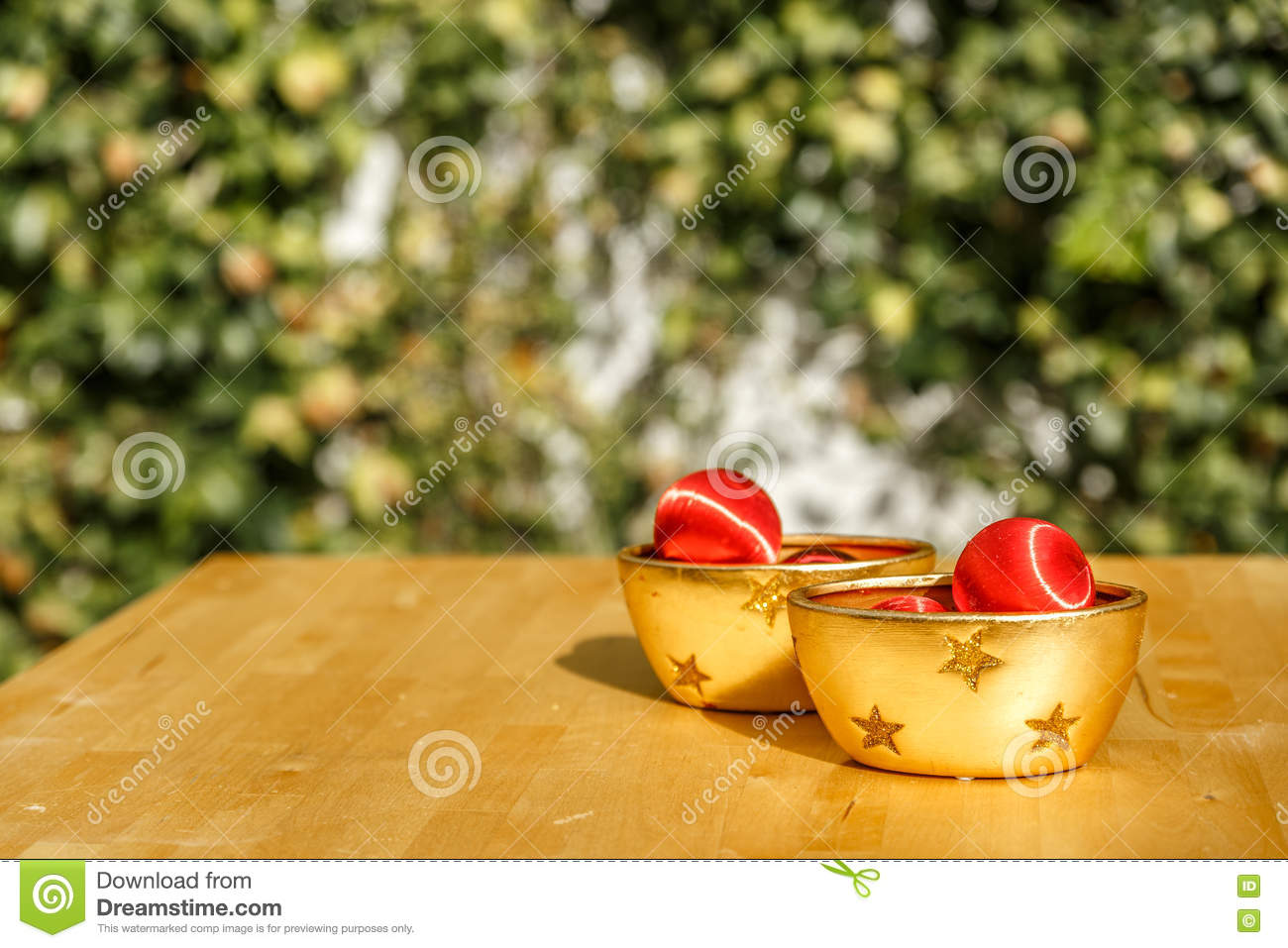 Red christmas balls and yellow decorative bowls on a wooden table