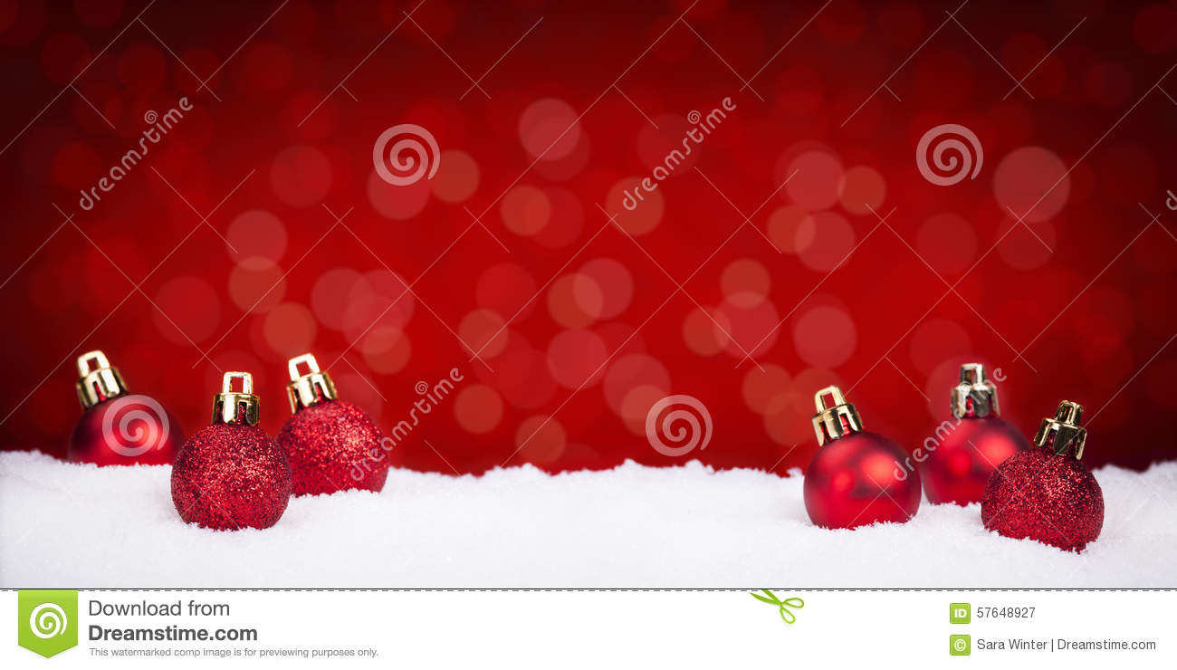 Red Christmas baubles on snow with a red background