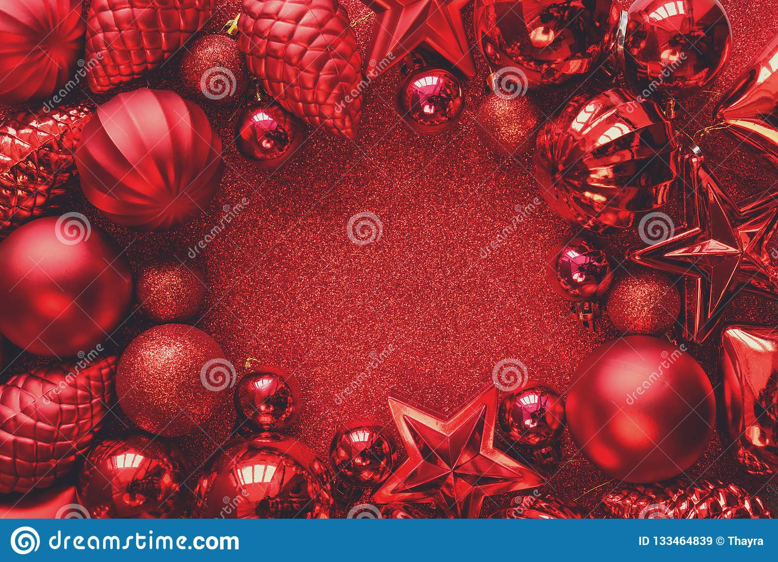 Red Christmas frame. Christmas balls, stars, cones and hearts on red sparkles background. Flat lay. Top view.