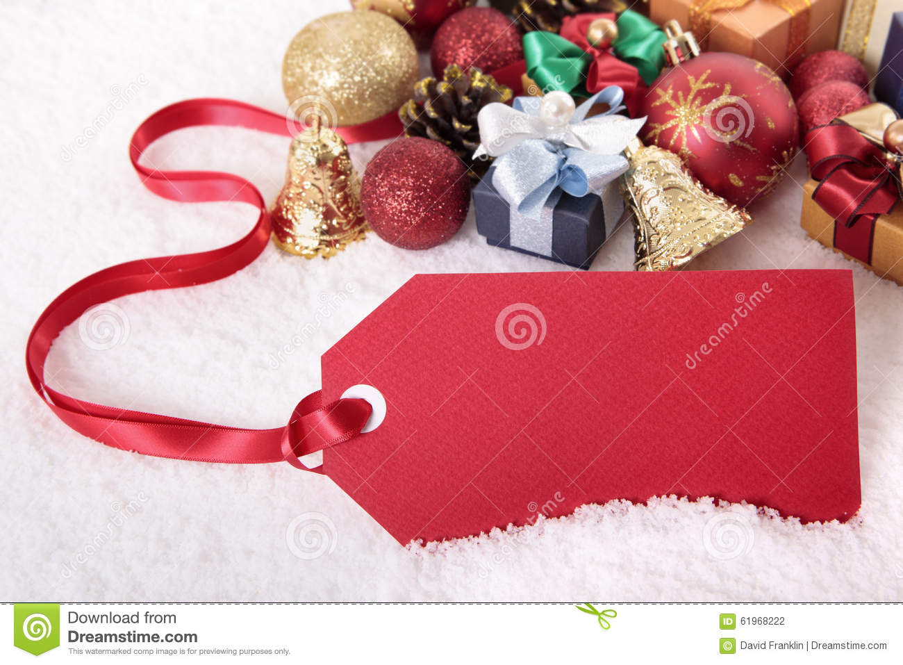 Red christmas gift tag on snow background with various