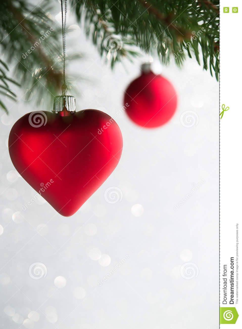 Red christmas ornaments heart and ball on the xmas tree on glitter bokeh background.