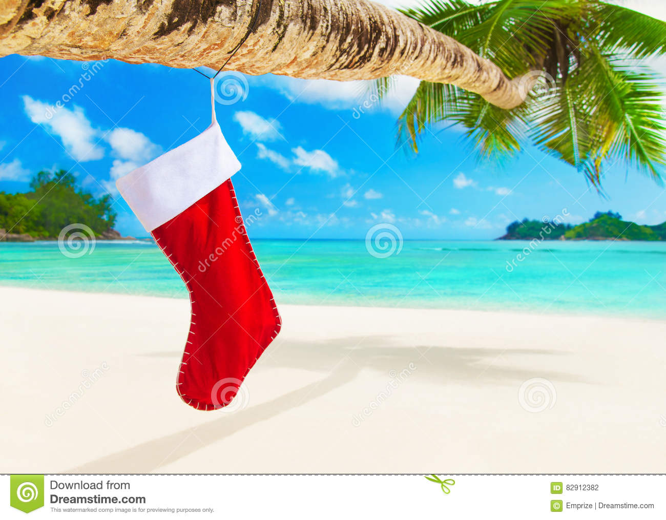 Red Christmas Sock With Gifts On Palm Tree At Tropical Beach