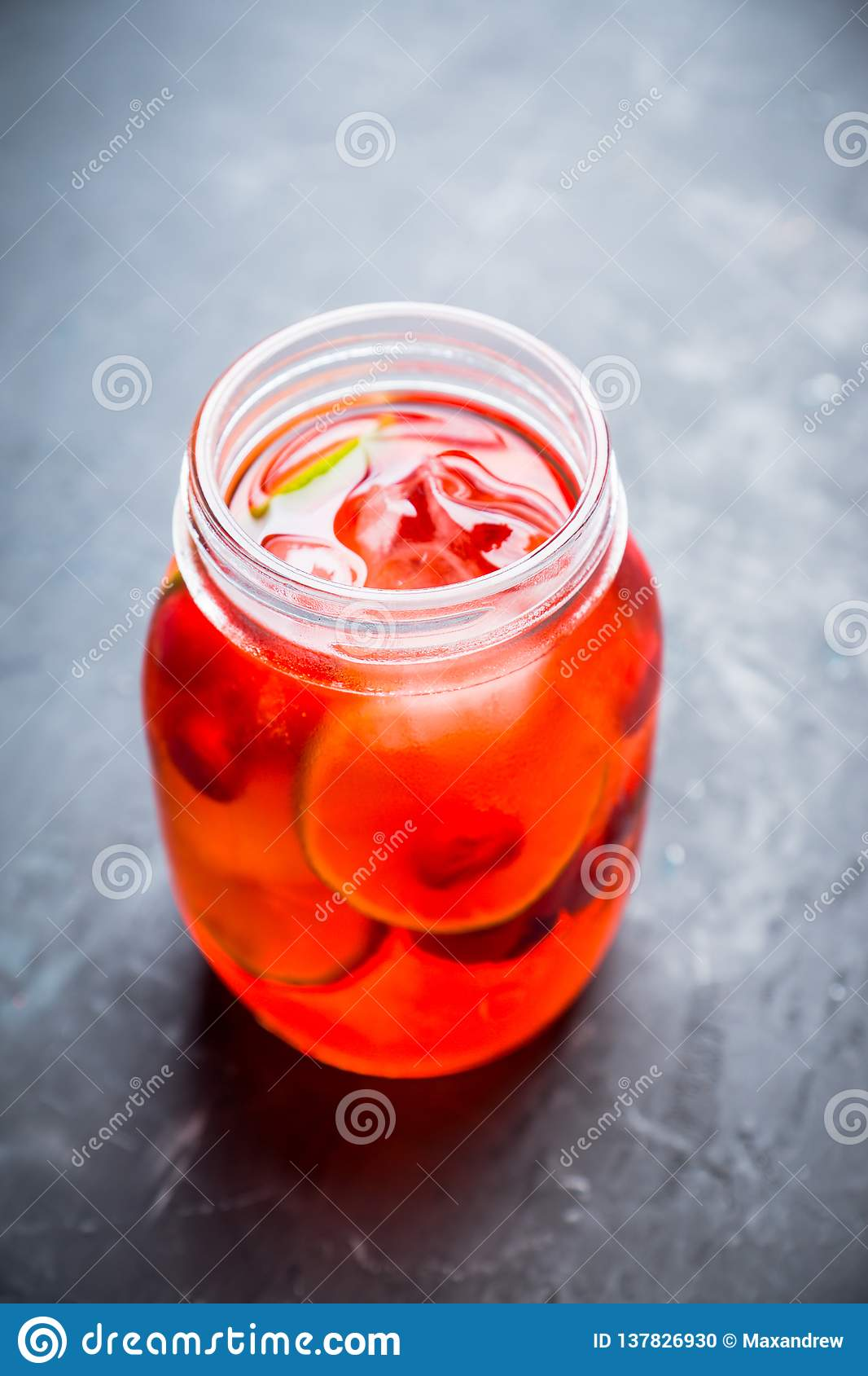 Red cocktail with cherry and lime in jar on the rustic background