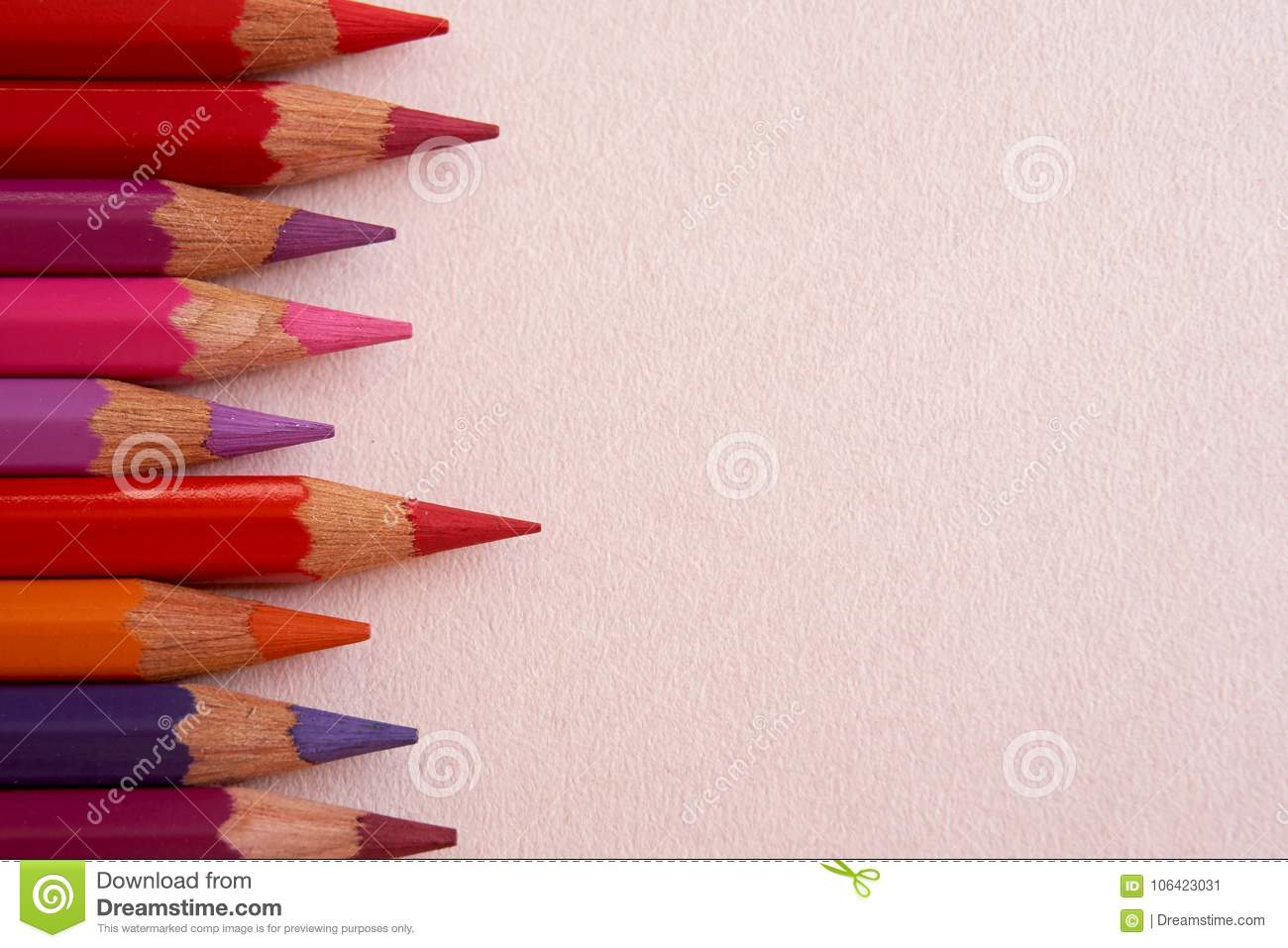 Red colored pencils over a pink background.