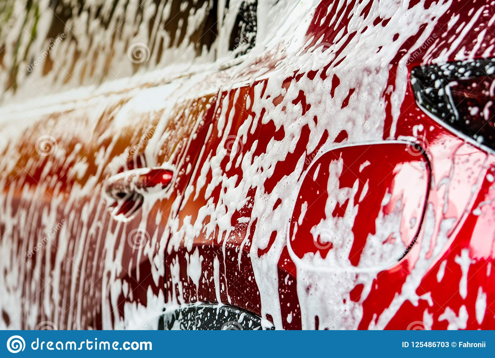 Red compact SUV car with sport and modern design washing with soap. Car covered with white foam. Car care service business concept