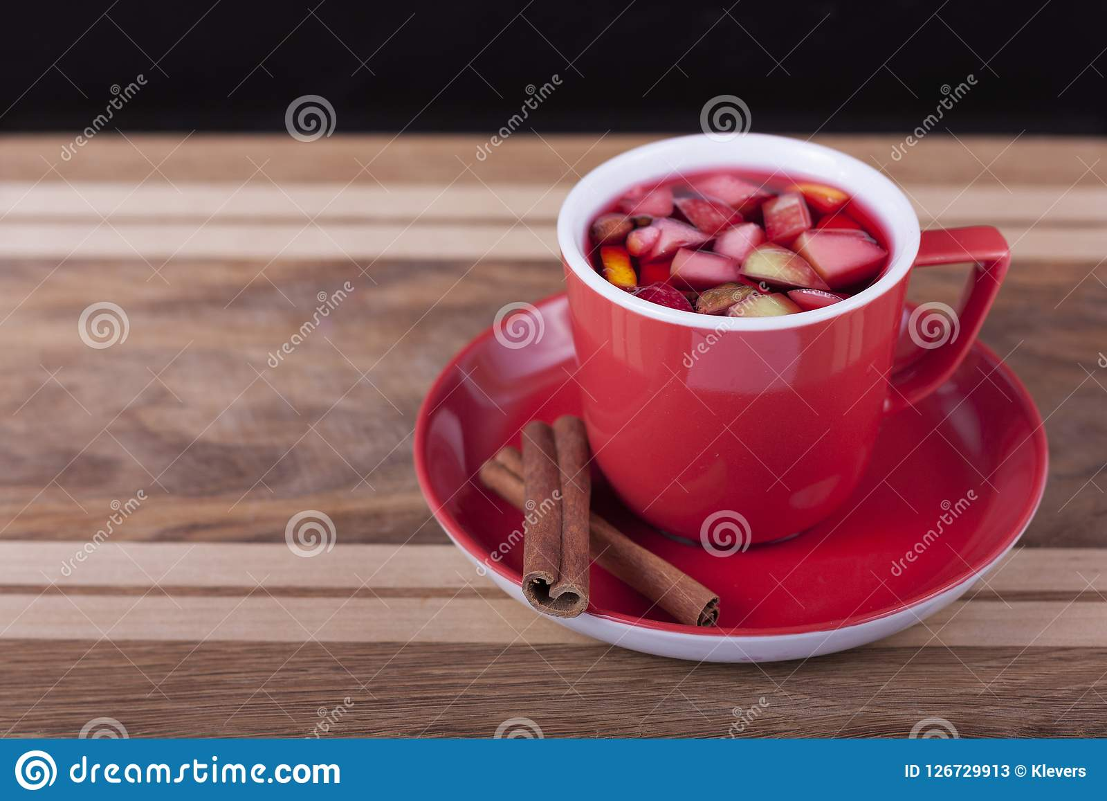 Red Cup with fruit tea on wooden background. Red Cup with saucer and cinnamon sticks on wooden background . Fruit tea Stock Photos