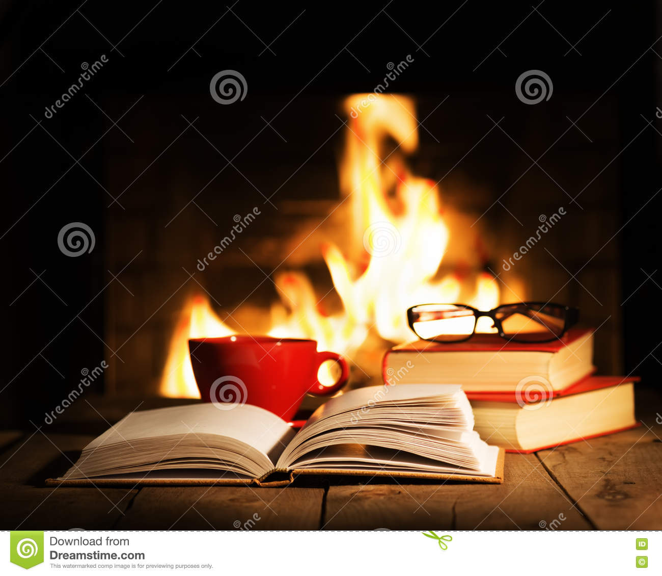 red cup and old books on wooden table near fireplace stock photo