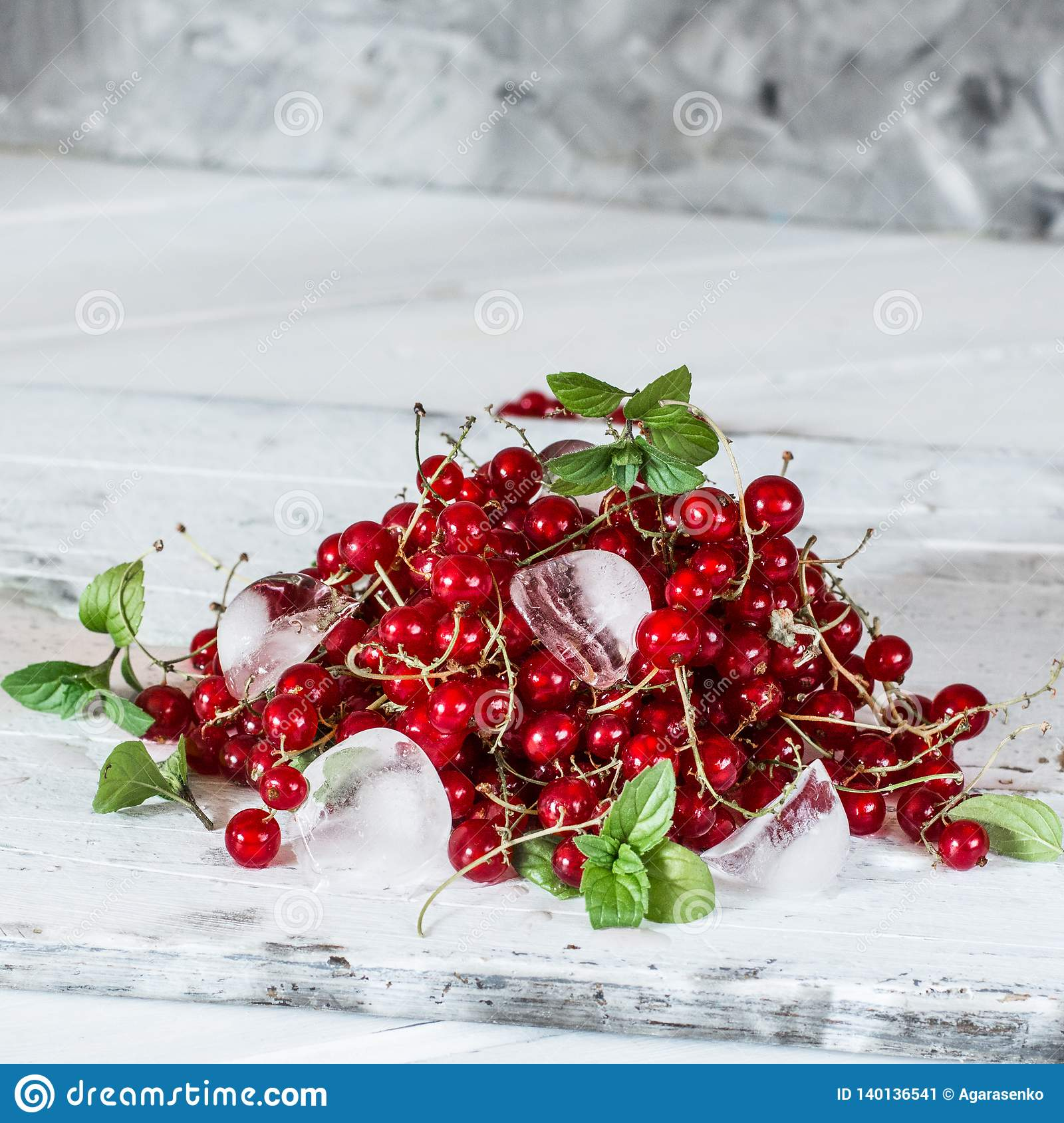 Red currant with ice and green leaves on white wooden background. Still life of food. Cubes of ice with berries.