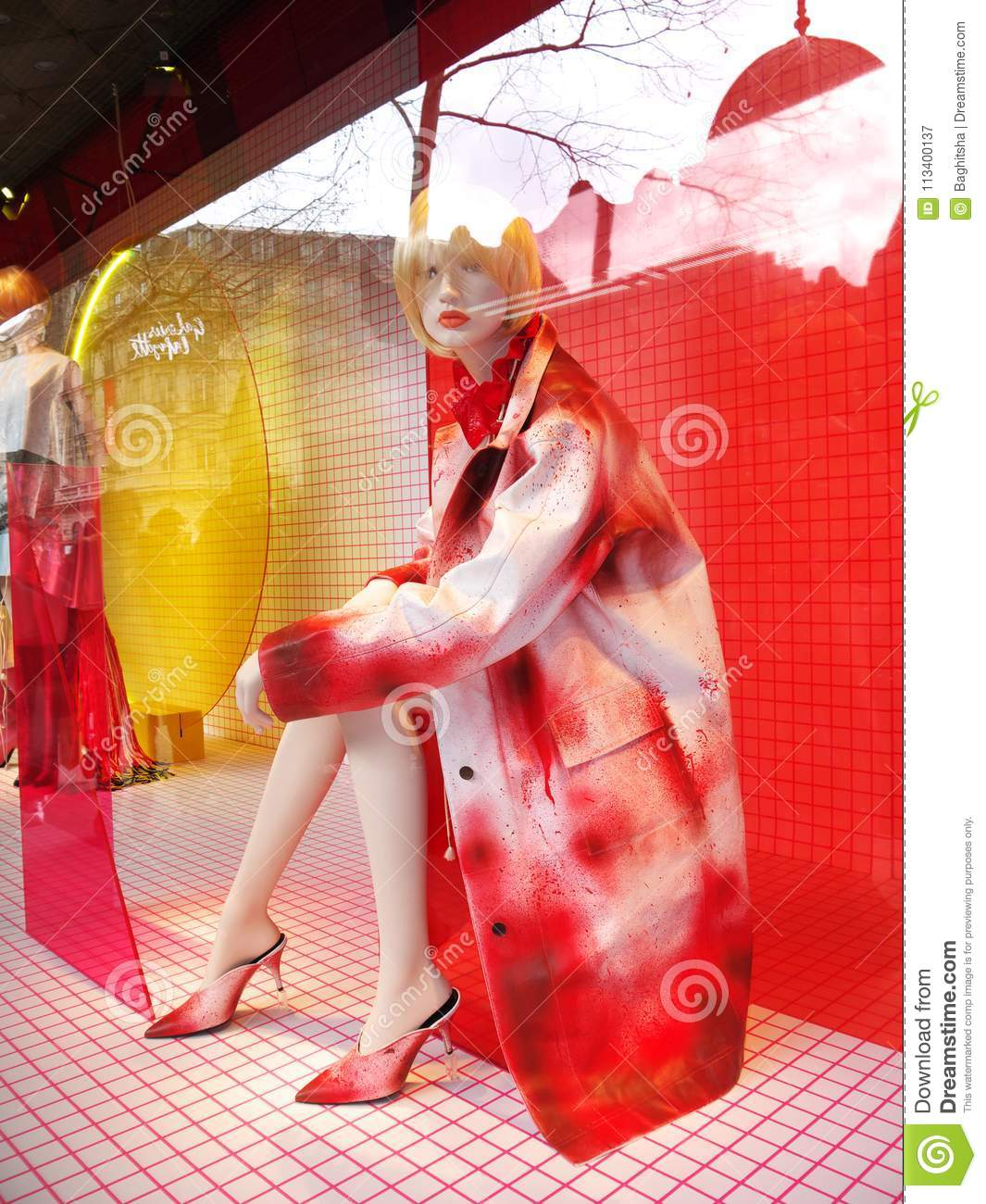 fa766904c583 A red dabbled Calvin Klein raincoat and high heel shoes on a mannequin in a  showcase of the Galeries Lafayette department store. Trend 2018.