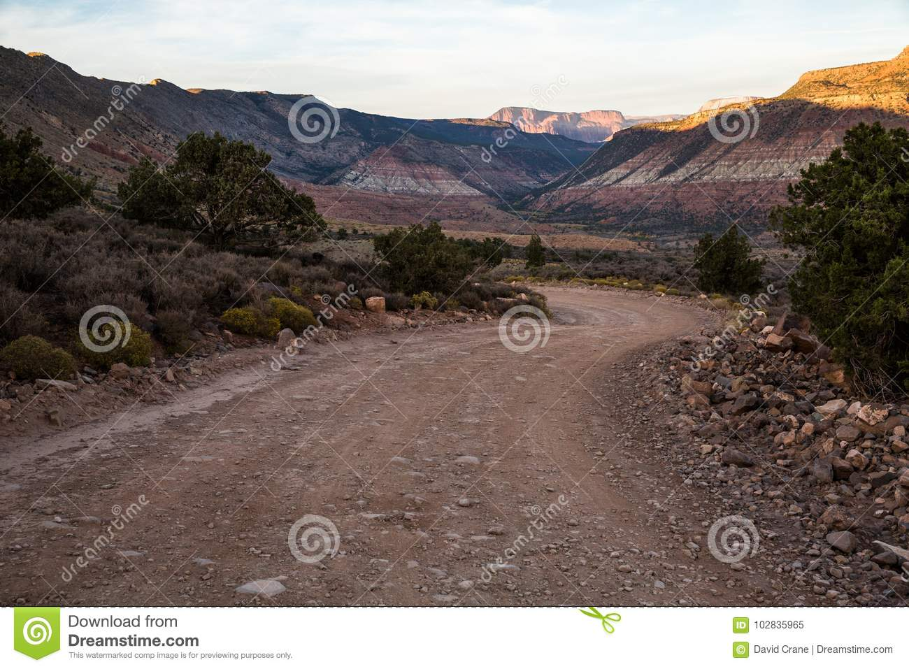 Winding road in shadow at sunset through the desert of Southern