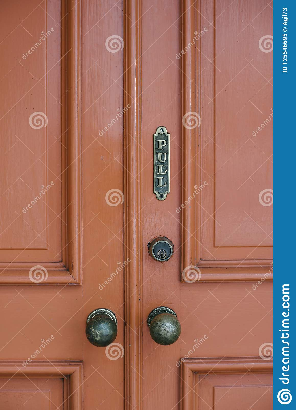 Old Red Door with Pull Sign and Old Door Knobs
