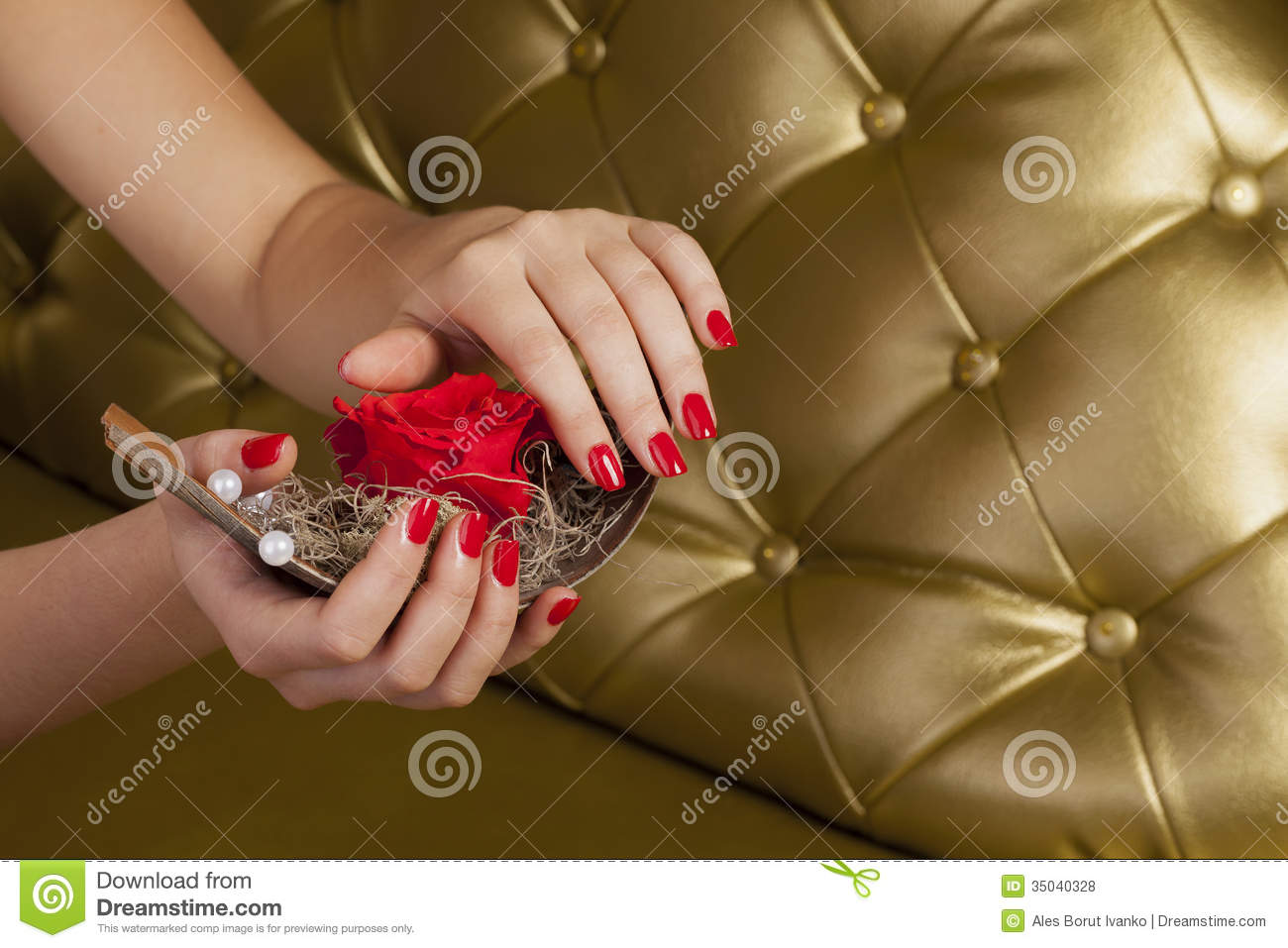 Red finger nails holding a boat with a rose
