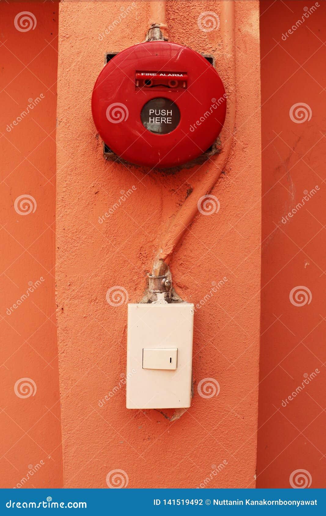 Red fire alarm on orange wall