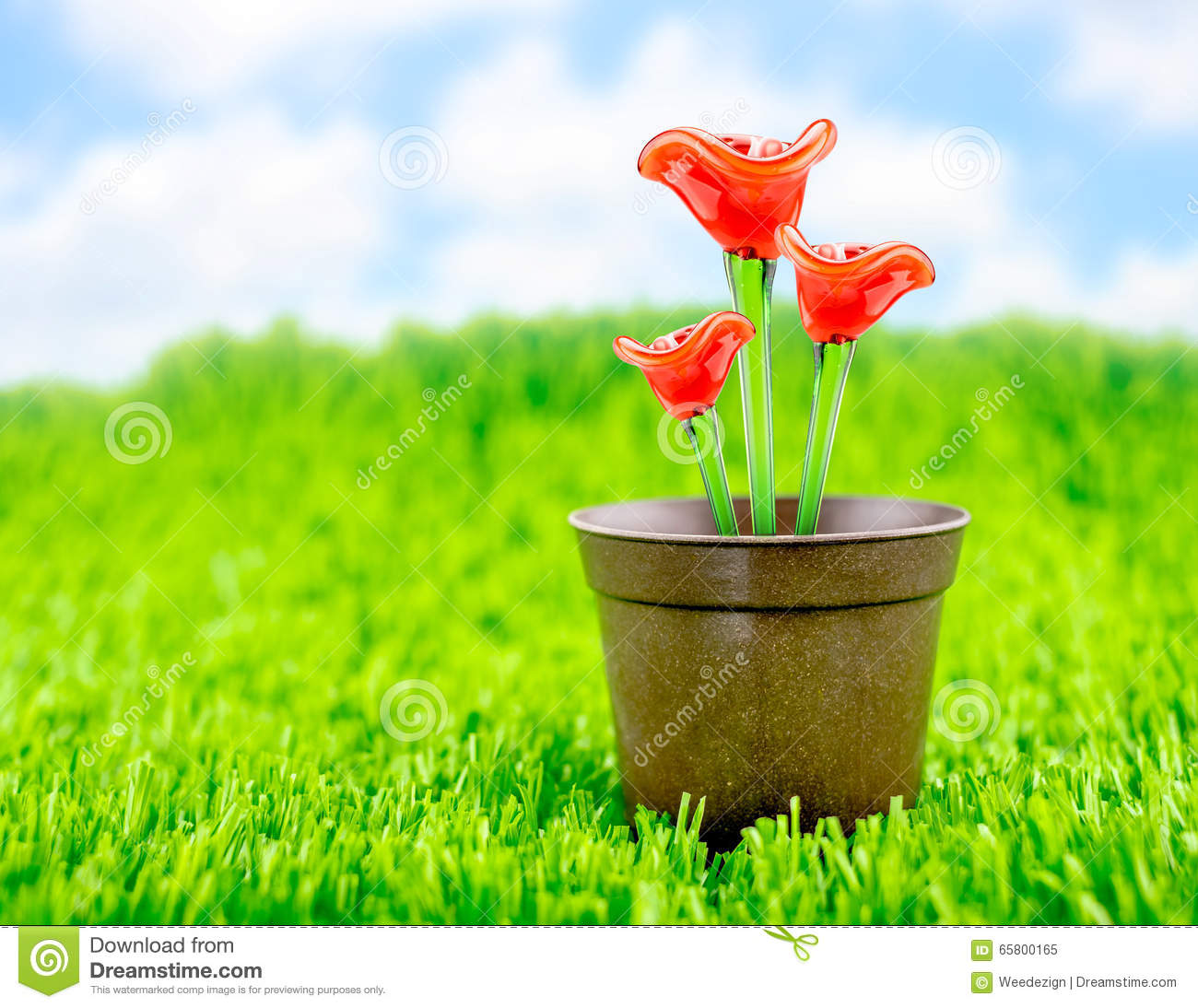 Red flower made of glass in brown flowerpot on green grass for Flowers made of glass