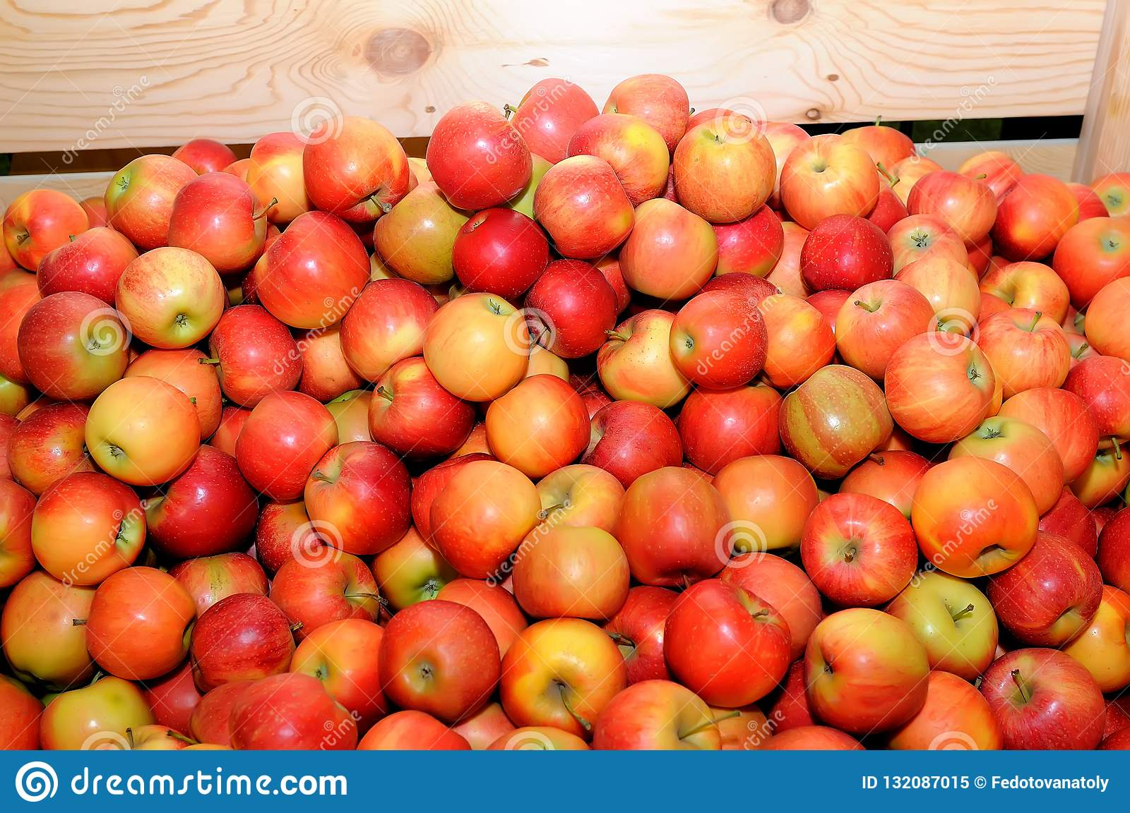 Red fresh apples in a pile on a wooden box