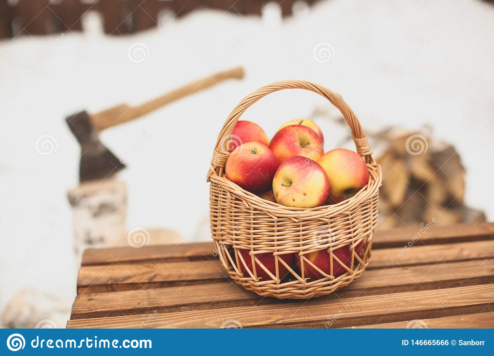 Red garden apples in a wicker picnic basket, on a wooden bench on a winter day, close-up. In the background, fuel wood and an axe