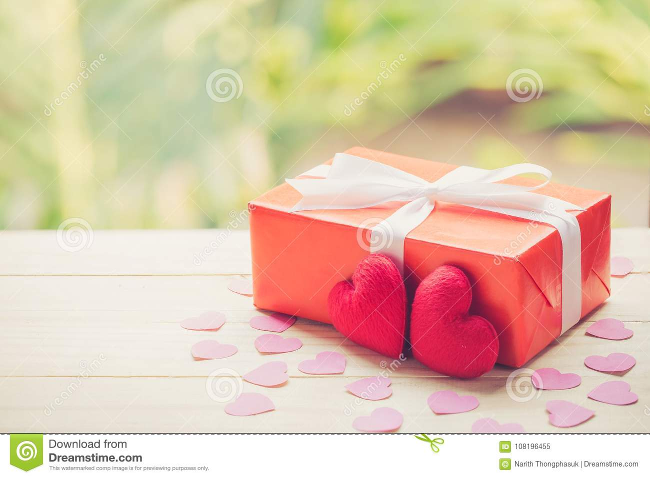 Red gift box and heart shape on wood table top with nature green blur bokeh background.