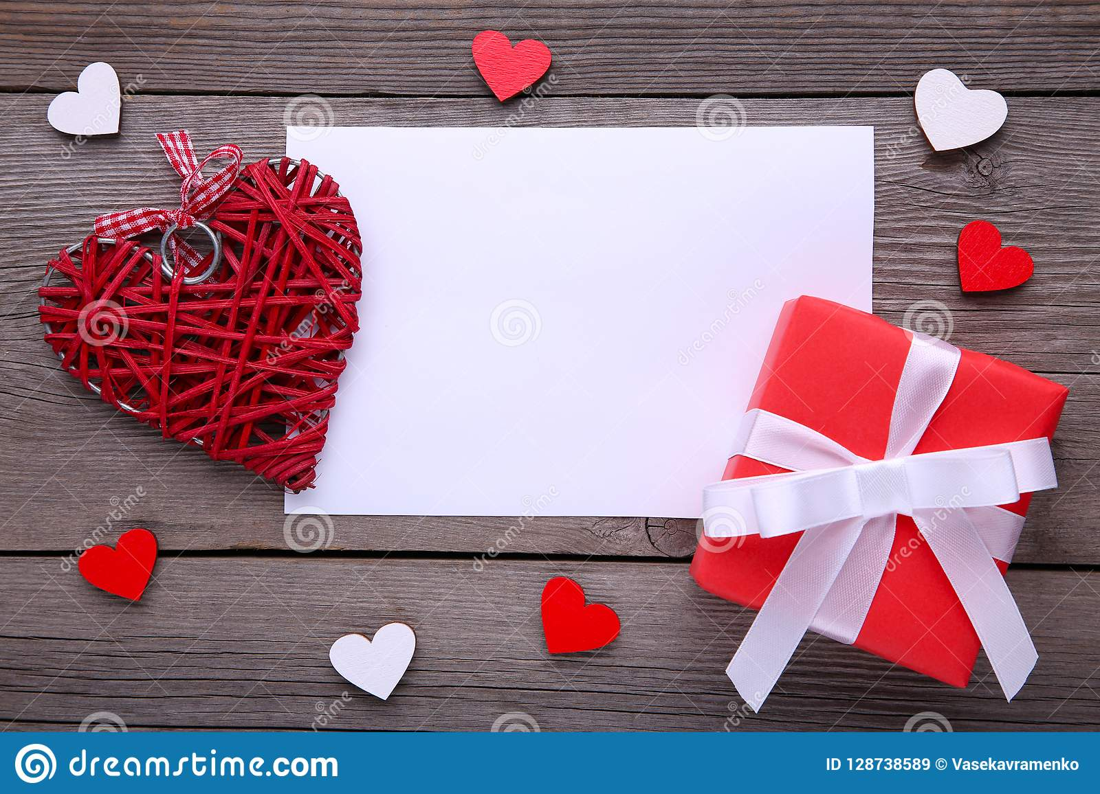 Red gift box with hearts on grey background
