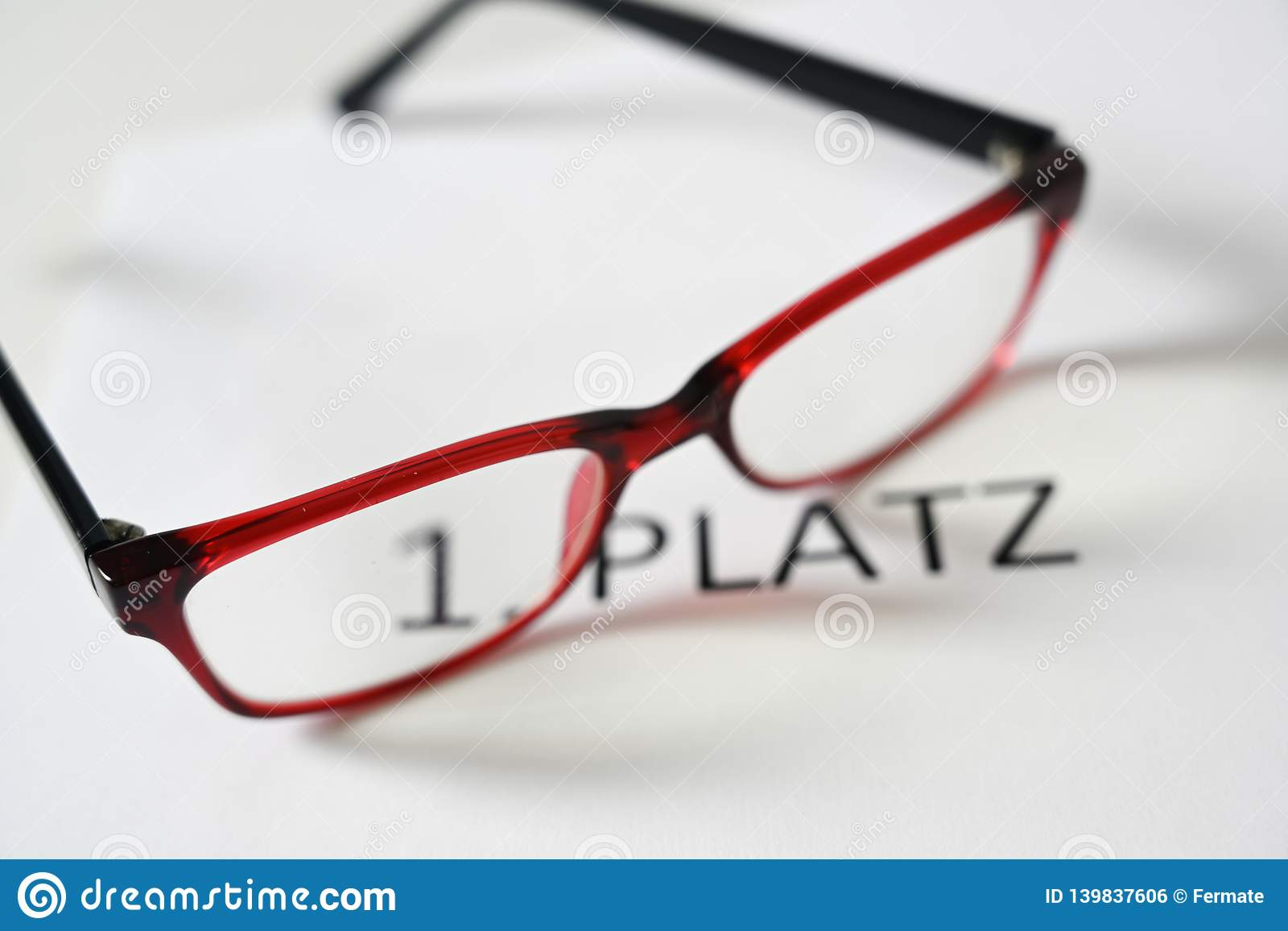 Red glasses above the german text 1 Platz, that means first place, competition jury concept