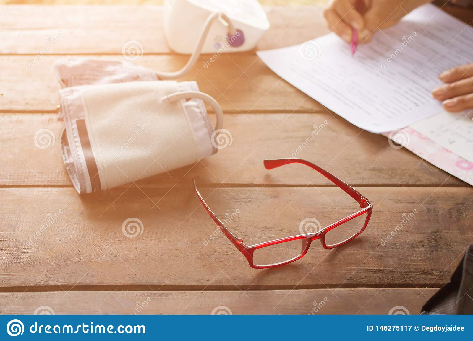 Red glasses with Blood Pressure Monitors with Blood Pressure Monitors, Woman holding pens to write inspection reports