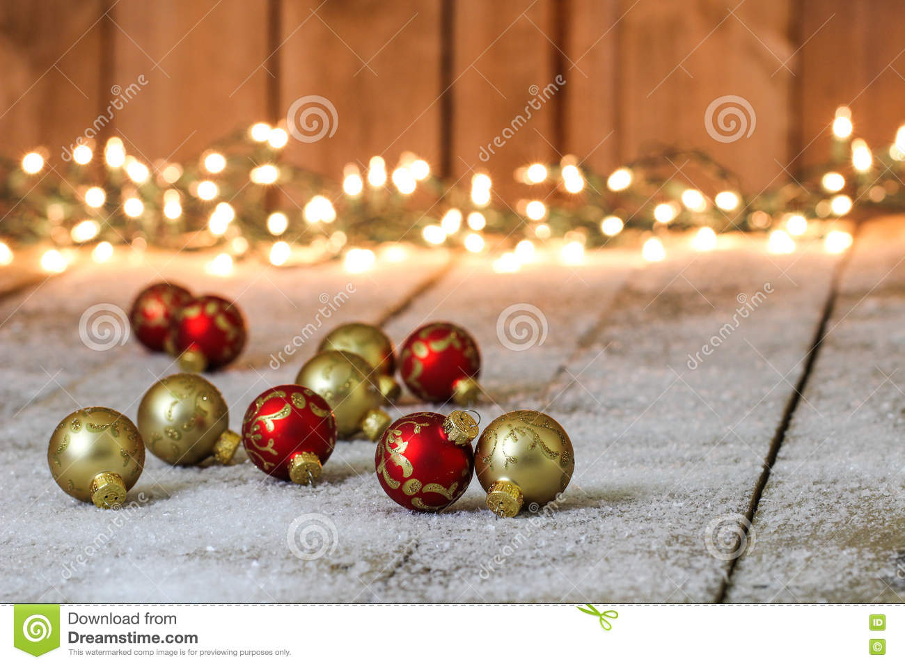 red gold christmas ornaments snowy background holiday snow covered rustic wood lights 77971019