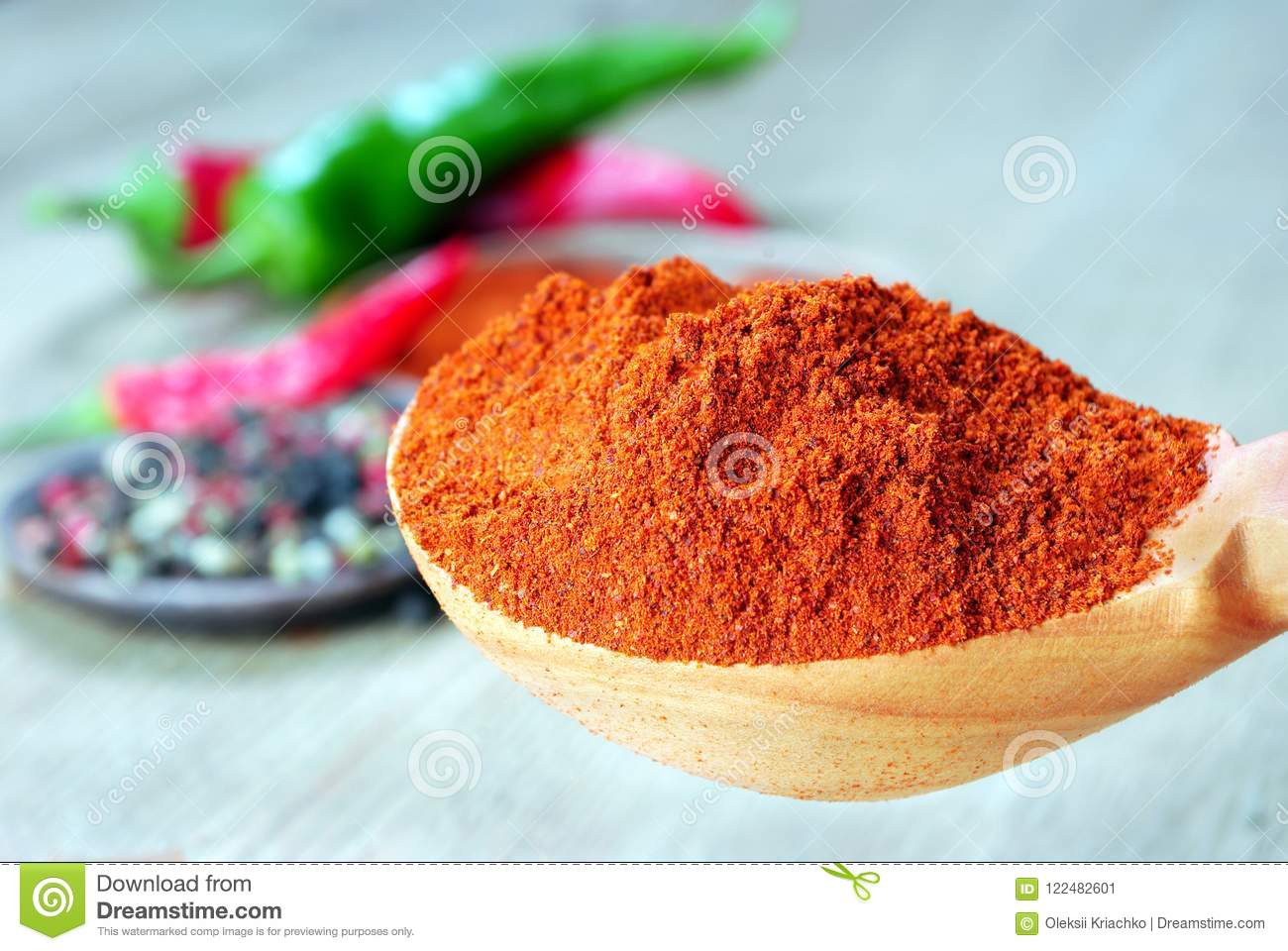 Red ground pepper in a wooden spoon. close up.