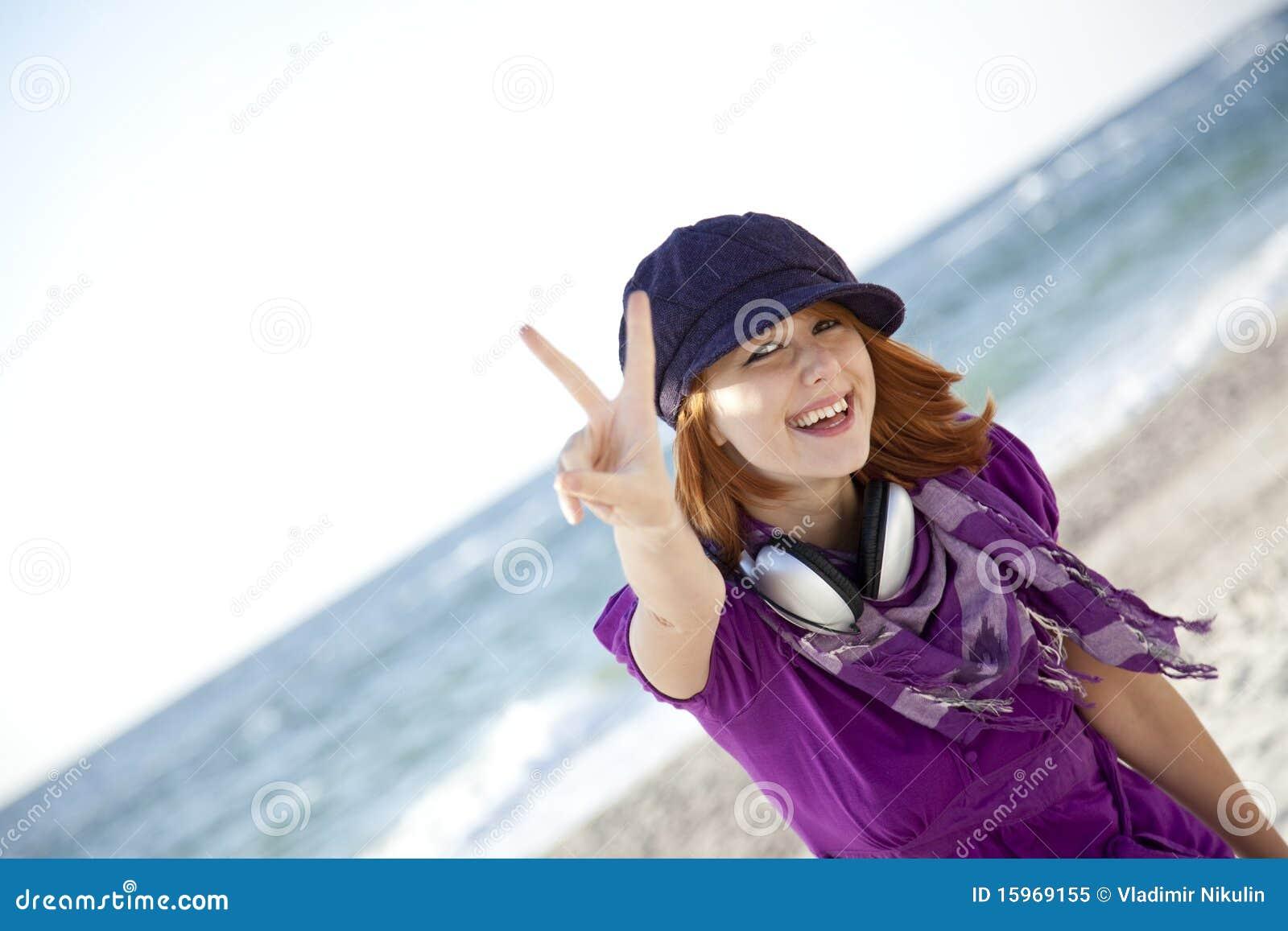 Red-haired девушка с наушниками на пляже.