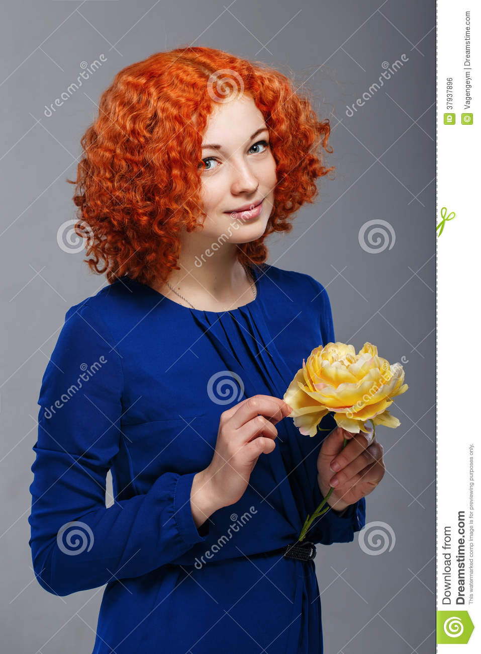 Attractive young red-haired girl in a blue dress holding in her hands a  yellow flower 452c7c170