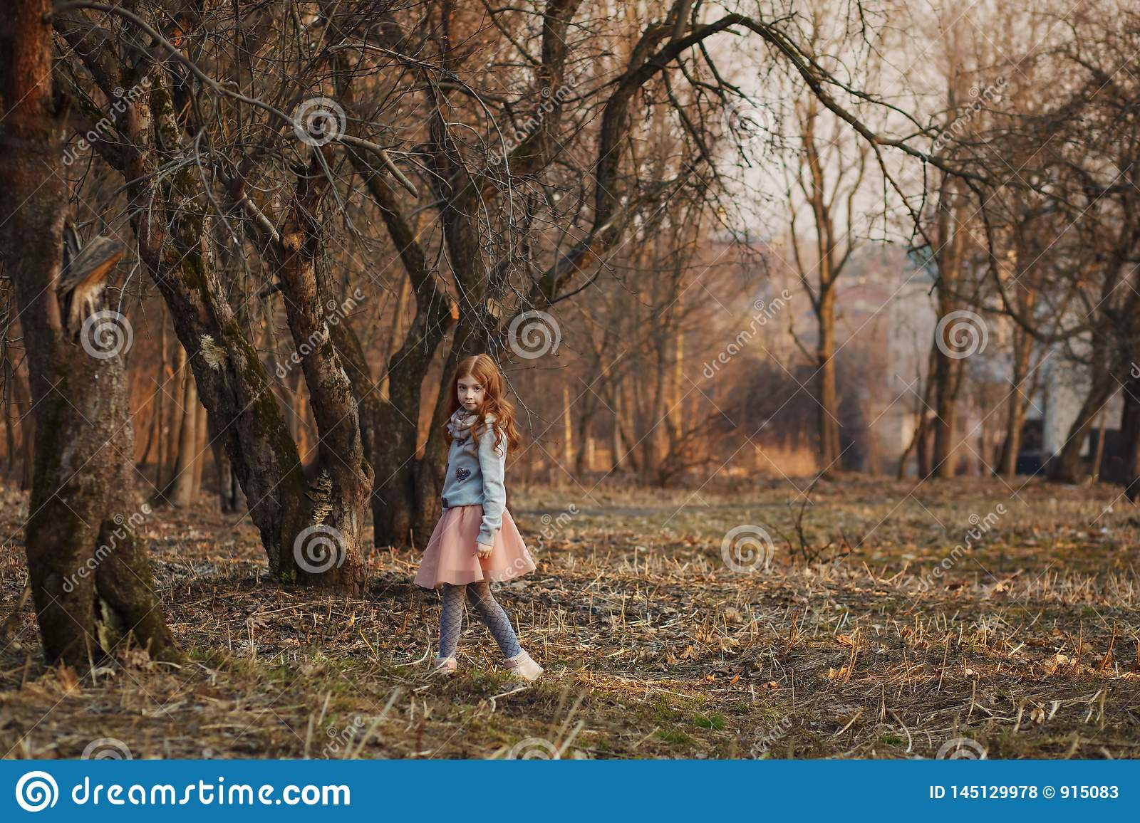 Red-haired girl with freckles in a park. Spring or Autumn. Happy carefree childhood