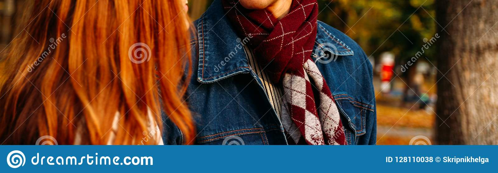 Red-haired girl and a guy in a denim jacket with a checkered scarf are walking in the autumn park, forest. close-up, brown scarf w