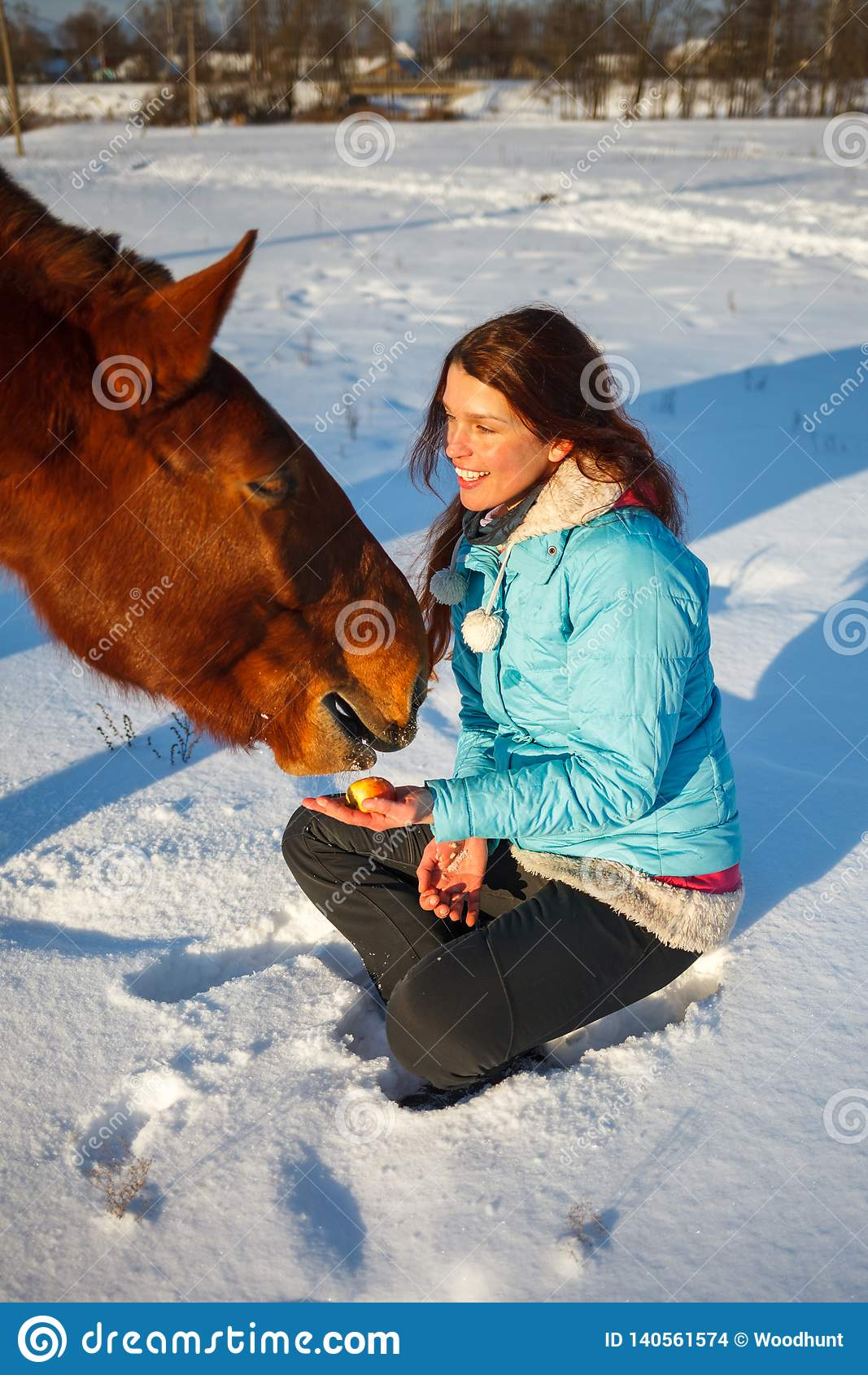 Red-haired girl in a snowy field feeds an apple from hands