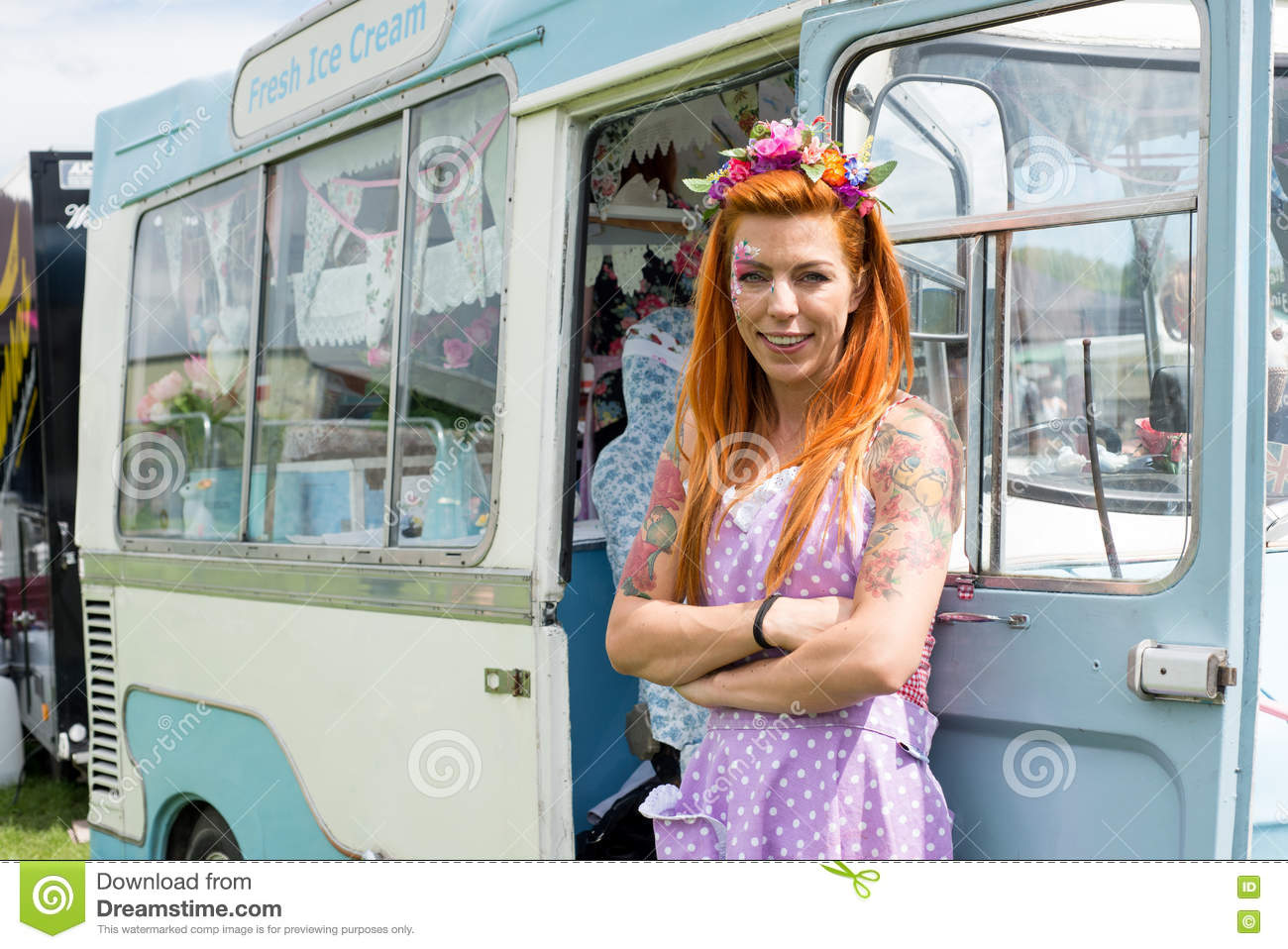 Red haired lady standing with vintage ice cream truck