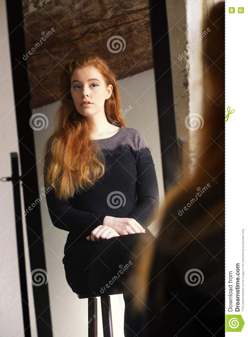 Red Haired Woman In Black Dress Looking At Herself In A