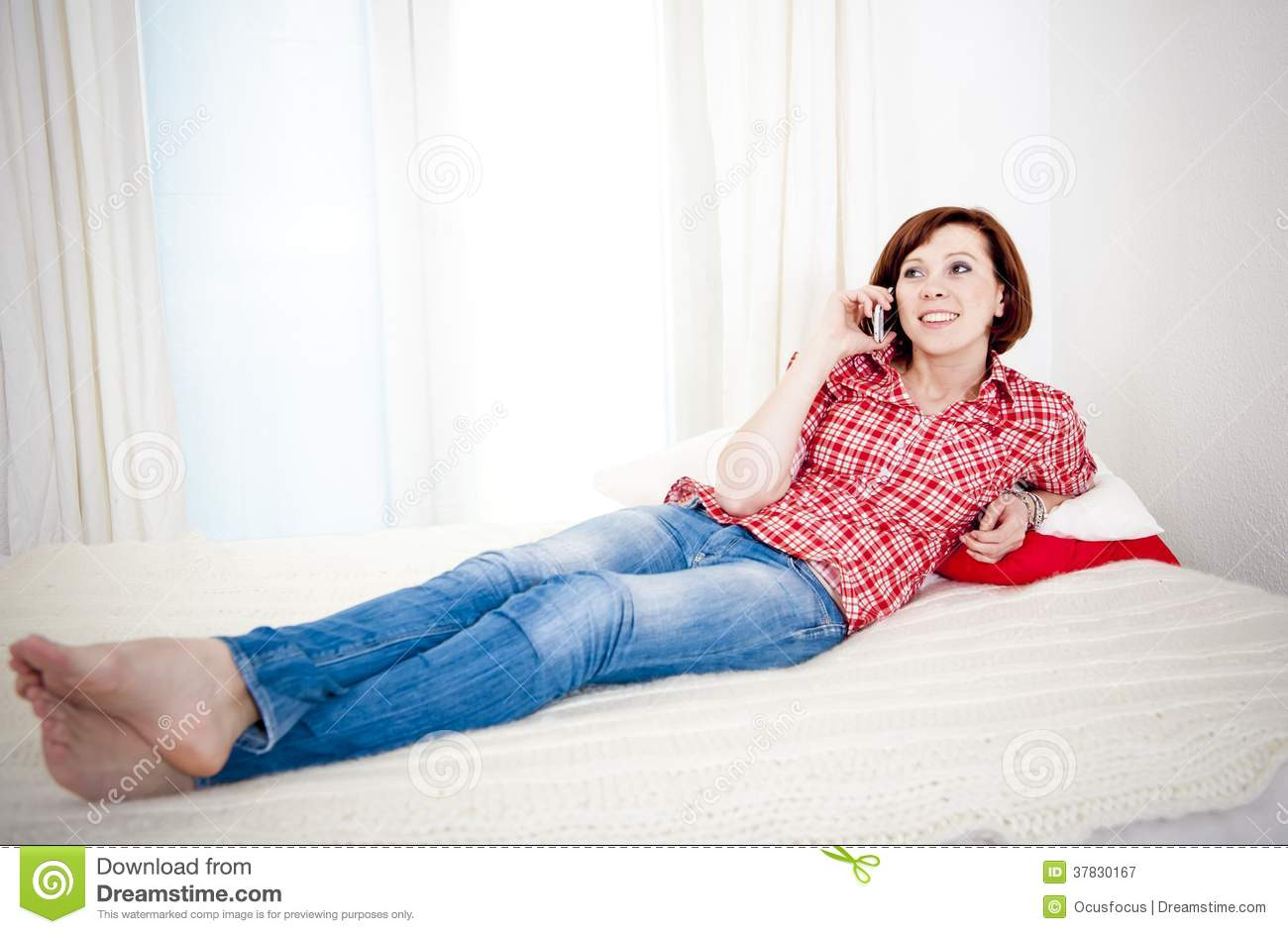 Red Haired Woman Lying Down On Couch Talking On Mobile ...