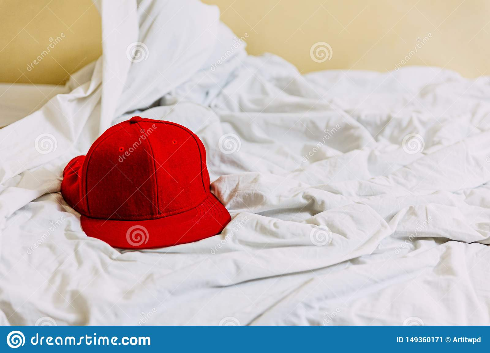Red hat on the left side over white blanket on the bed with yellow background