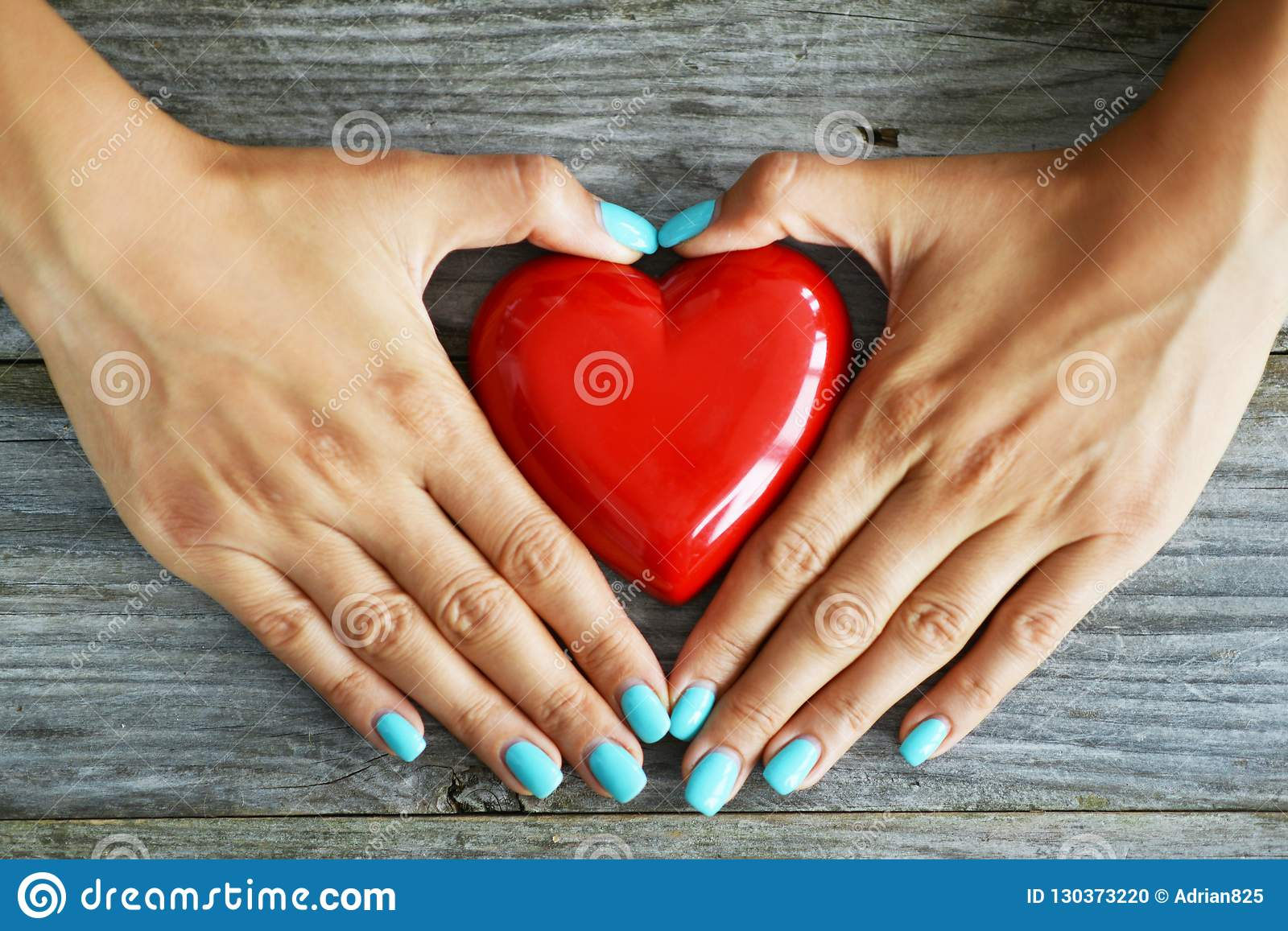 Red heart as love symbol in woman hand on rustic wooden background