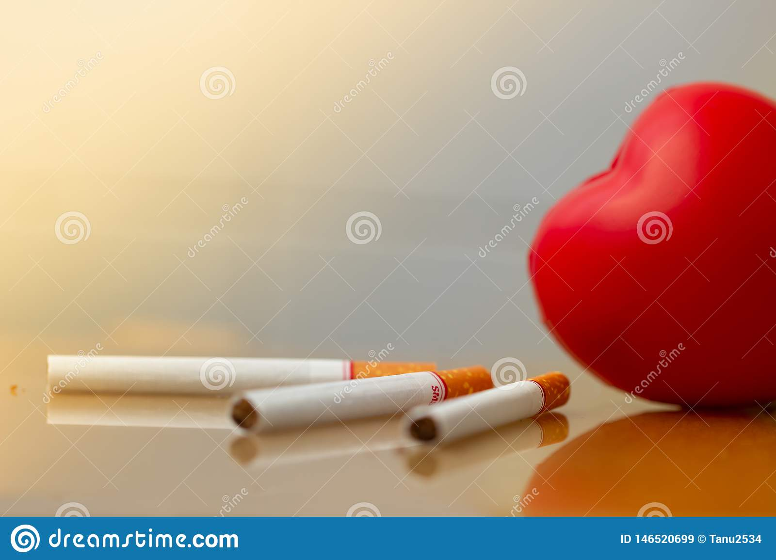 Red heart and cigarettes. Smoking cigarette destroying health. heart disease.