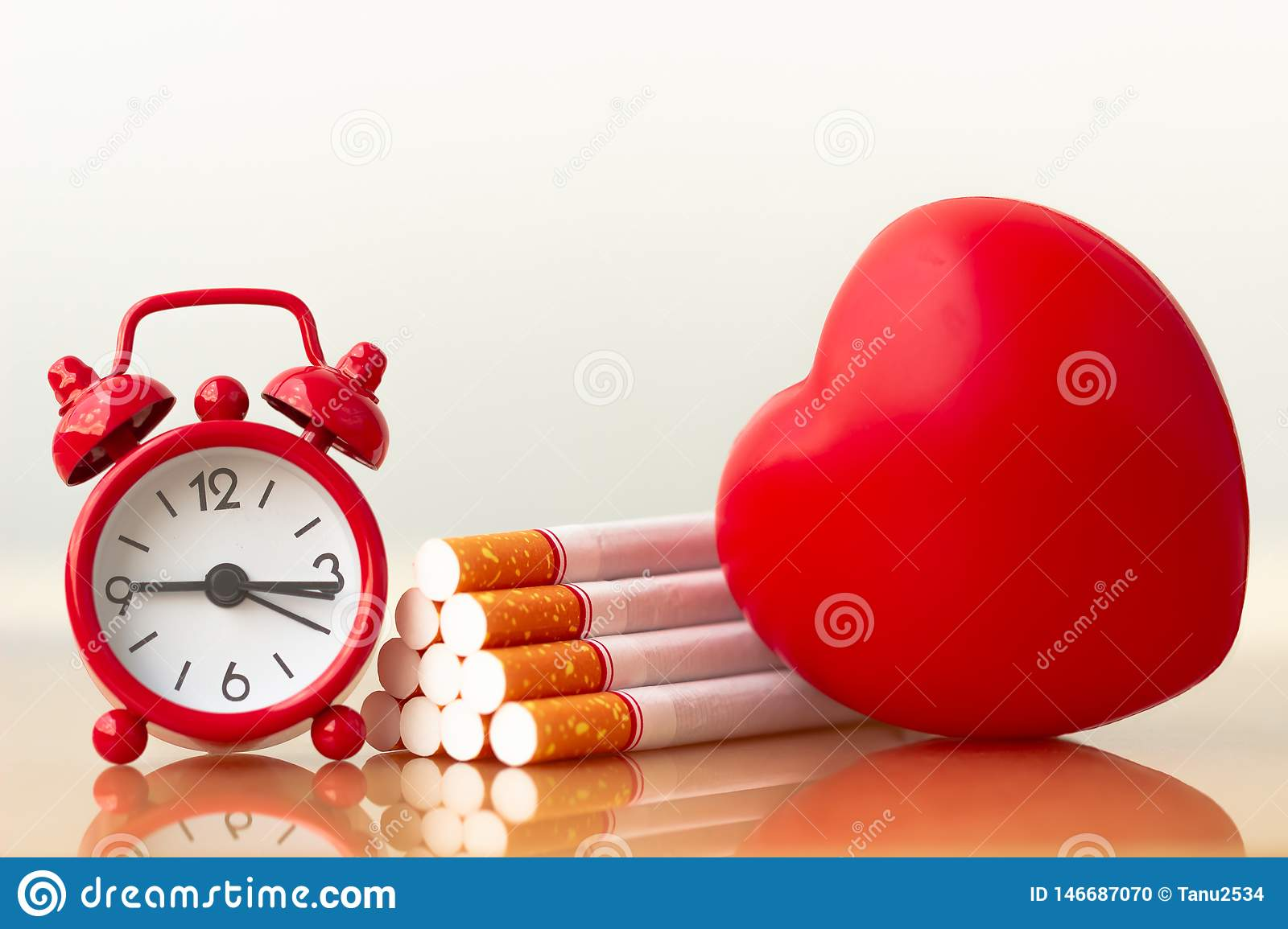 Red heart and cigarettes. Smoking cigarette destroying health.