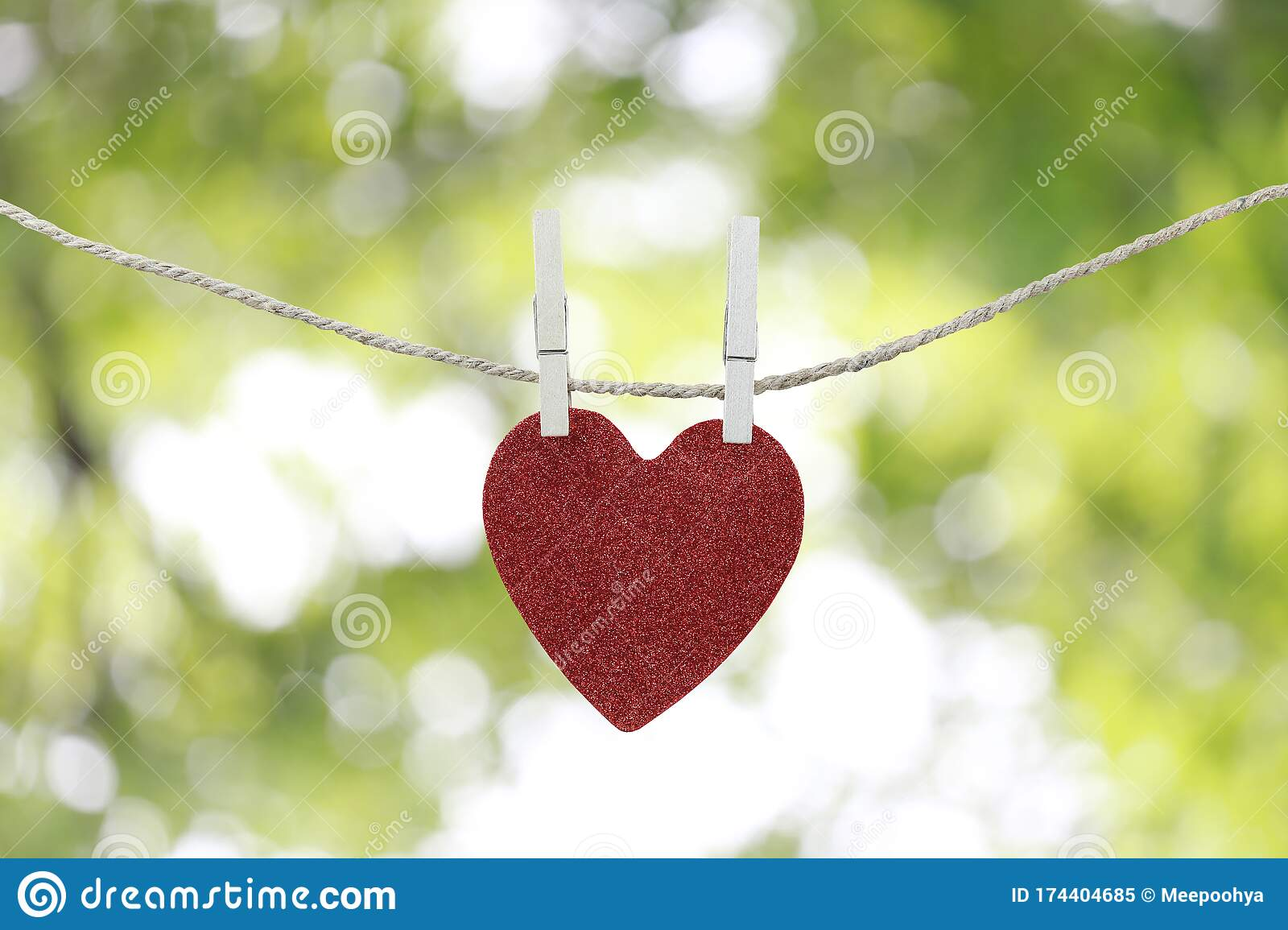 Red Heart Hanging On A Hemp Rope On The Green Bokeh Background Stock Image Image Of Natural Code 174404685