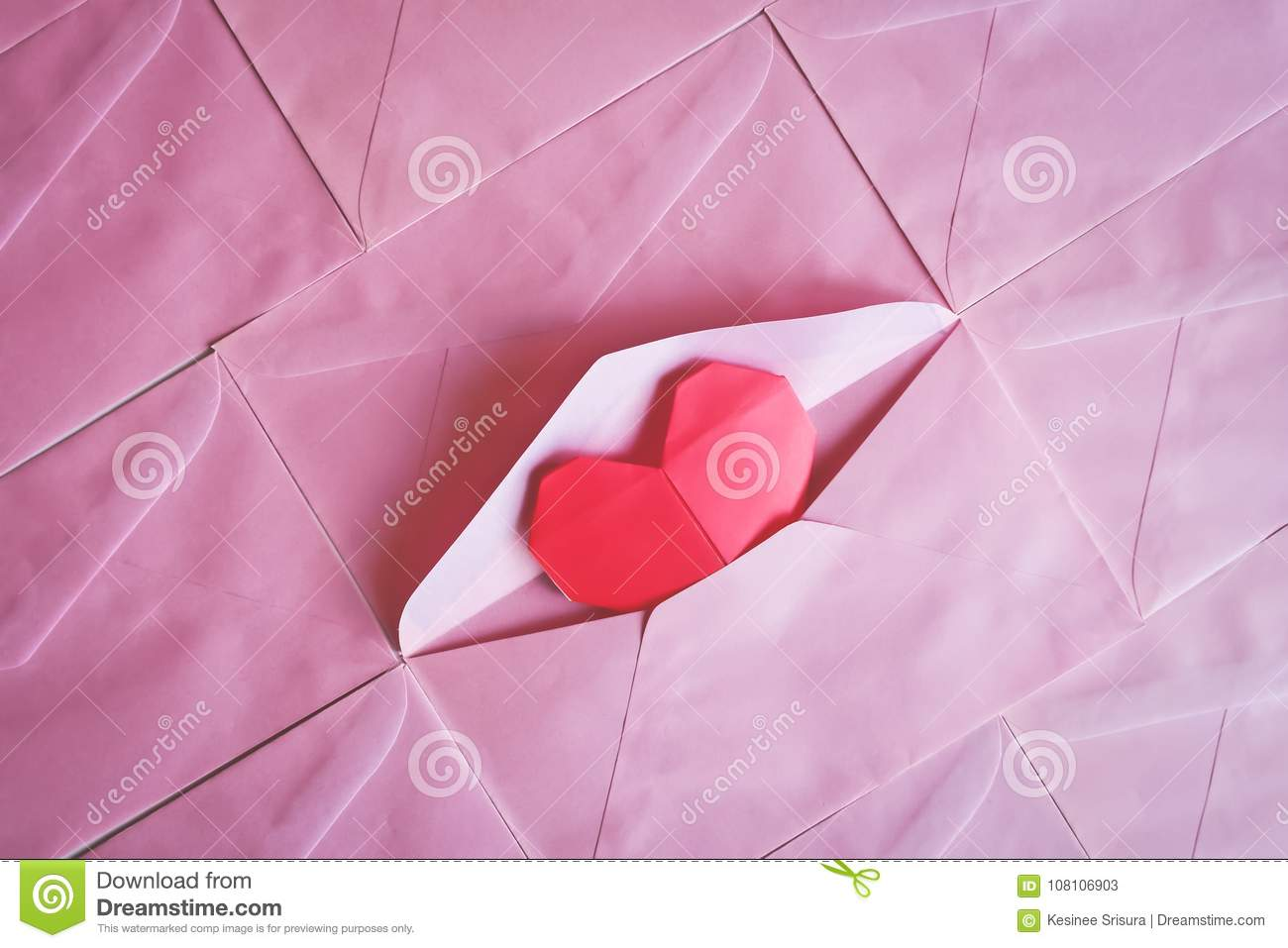 Red heart paper origami in pink envelope background