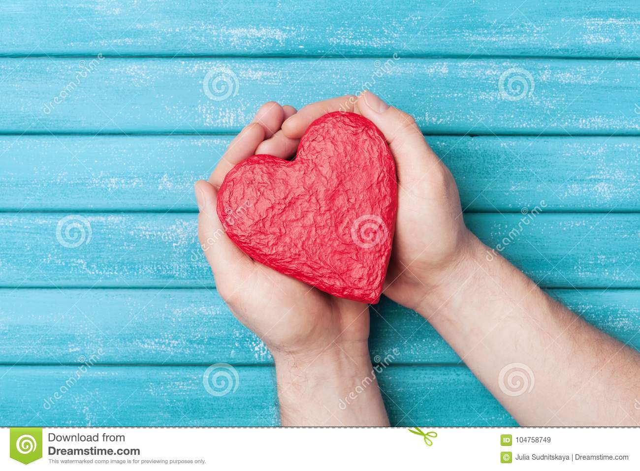 Red heart shape in hands top view. Healthy, donation organ, donor, hope and cardiology concept. Valentines day card.