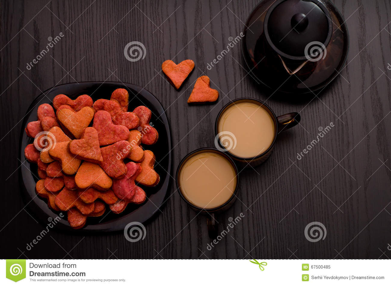 Red heart-shaped cookies, two cups of tea with milk and teapot. Valentine s Day